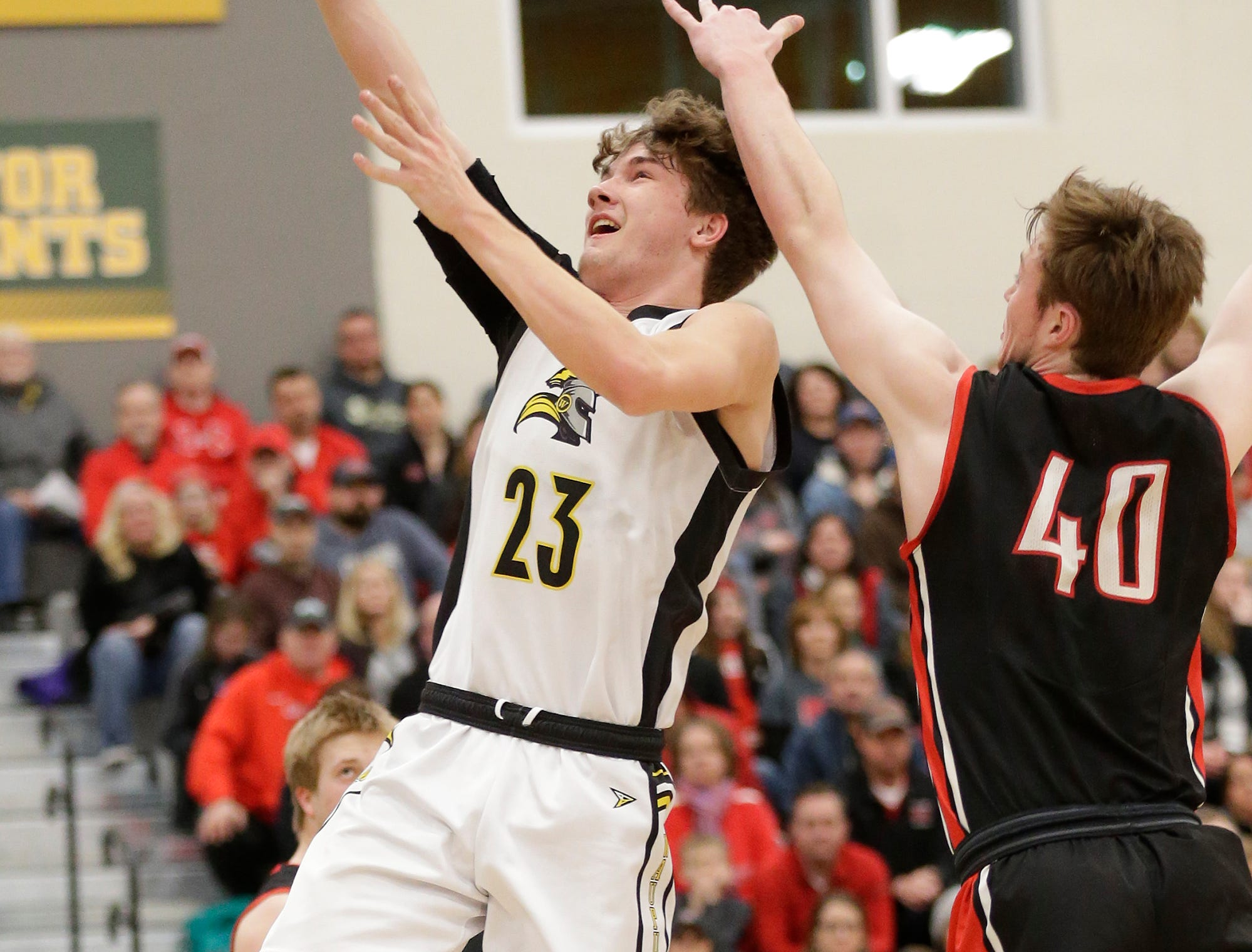 Waupun High School boys basketball's Reece Homan (23) goes up for a basket against Columbus High School's Ben Emler (40) during their WIAA division 3 sectional semi-final game Thursday, March 7, 2019 in Beaver Dam, Wis. Waupun won the game 79-36. Doug Raflik/USA TODAY NETWORK-Wisconsin