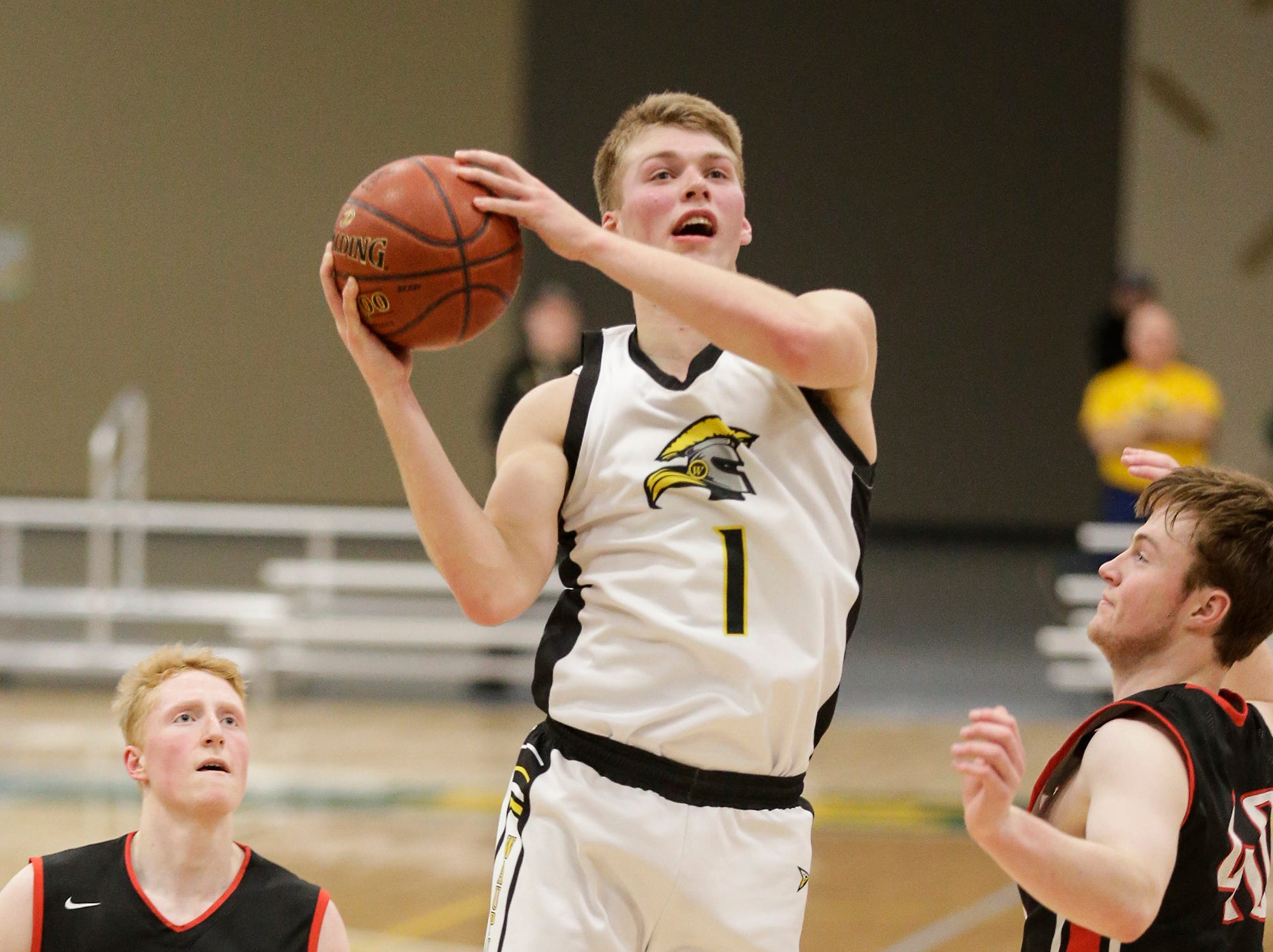 Waupun High School boys basketball's Marcus Domask (1) goes up for a shot between Columbus High School's Trent Casper (22) and Ben Emler (40) during their WIAA division 3 sectional semi-final game Thursday, March 7, 2019 in Beaver Dam, Wis. Waupun won the game 79-36. Doug Raflik/USA TODAY NETWORK-Wisconsin