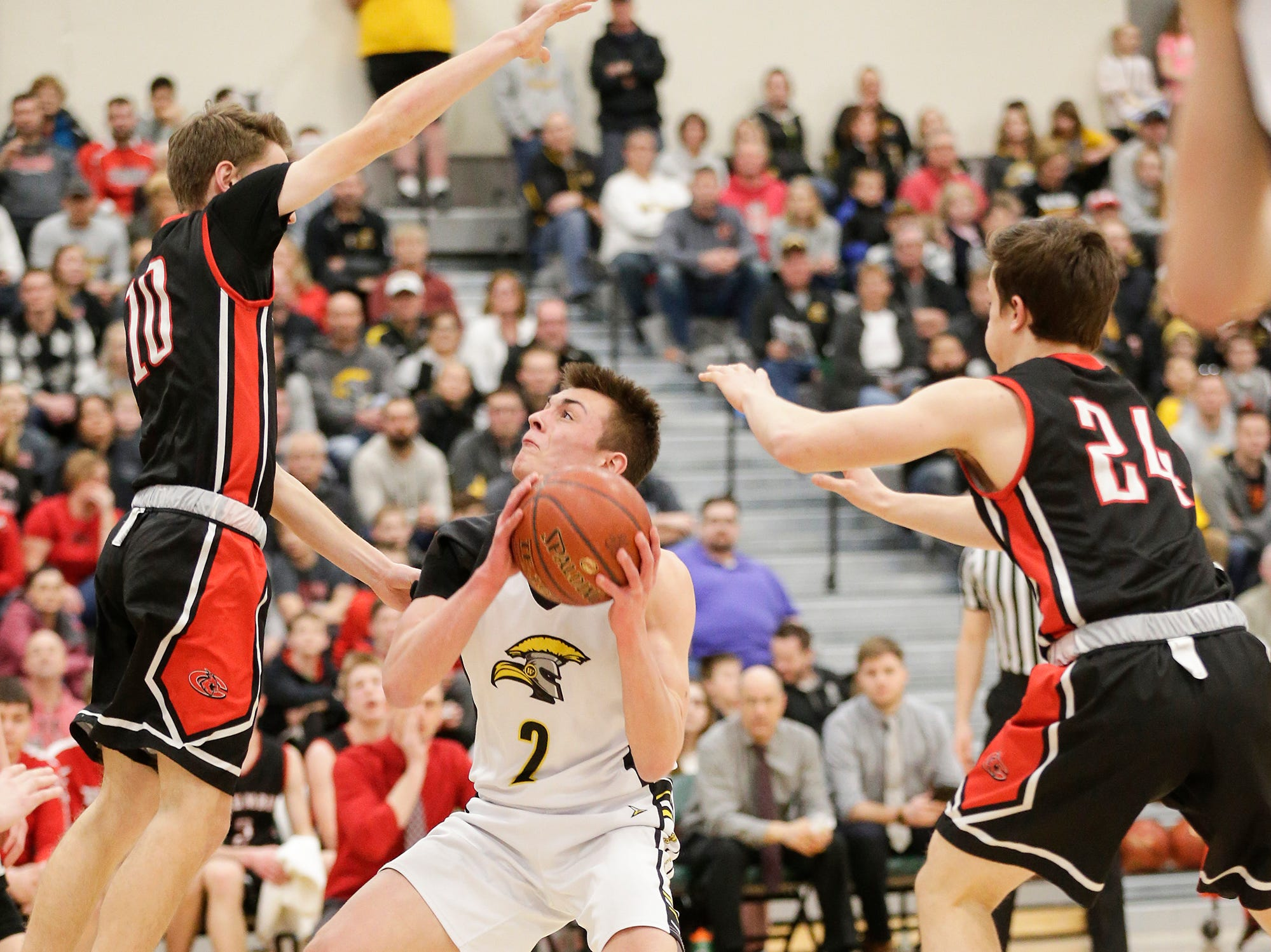 Waupun High School boys basketball's Trevor VandeZande (2) works against Columbus High School's Adam Zahn (10) and Caden Brunell (24) during their WIAA division 3 sectional semi-final game Thursday, March 7, 2019 in Beaver Dam, Wis. Waupun won the game 79-36. Doug Raflik/USA TODAY NETWORK-Wisconsin