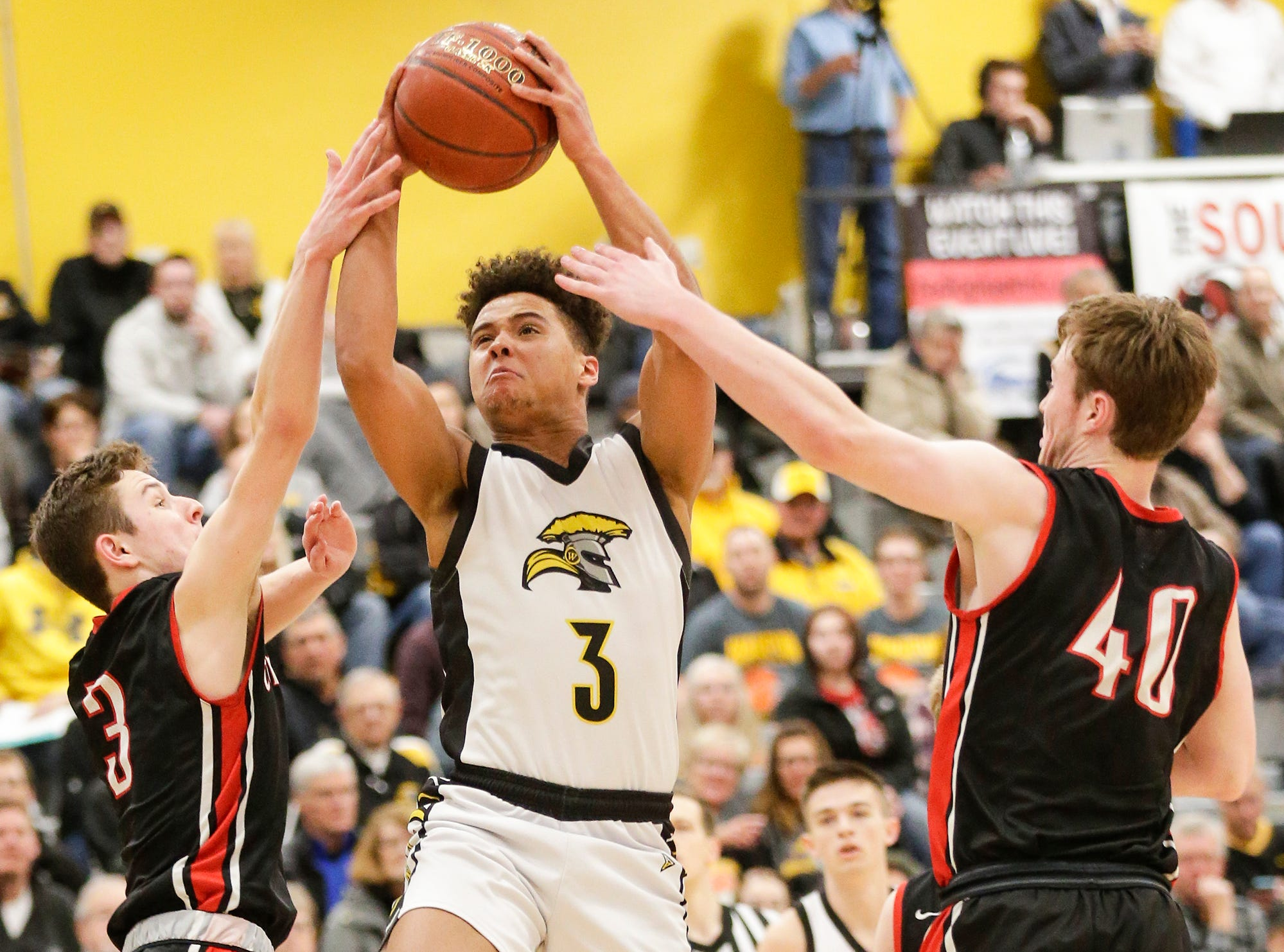 Waupun High School boys basketball's Quintin Winterfeldt splits Columbus High School's Caden Bieker (3) and Ben Emler (40) as he goes up for a basket during their WIAA division 3 sectional semi-final game Thursday, March 7, 2019 in Beaver Dam, Wis. Waupun won the game 79-36. Doug Raflik/USA TODAY NETWORK-Wisconsin