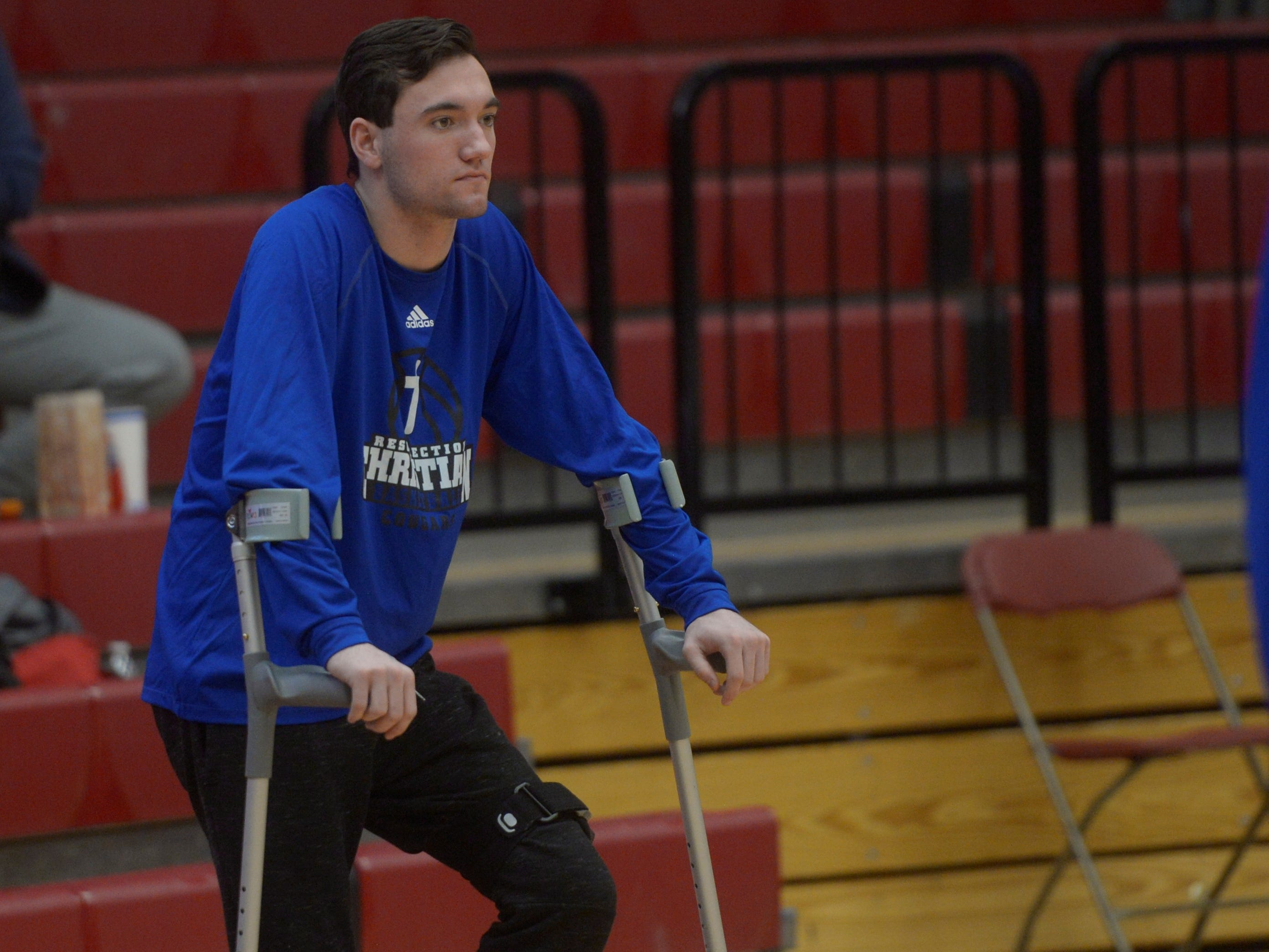 Injured Resurrection Christian player Colton Stahla watches his teammates warm up before a Class 3A quarterfinals game against Manual at the University of Denver on Thursday, March 7, 2019.
