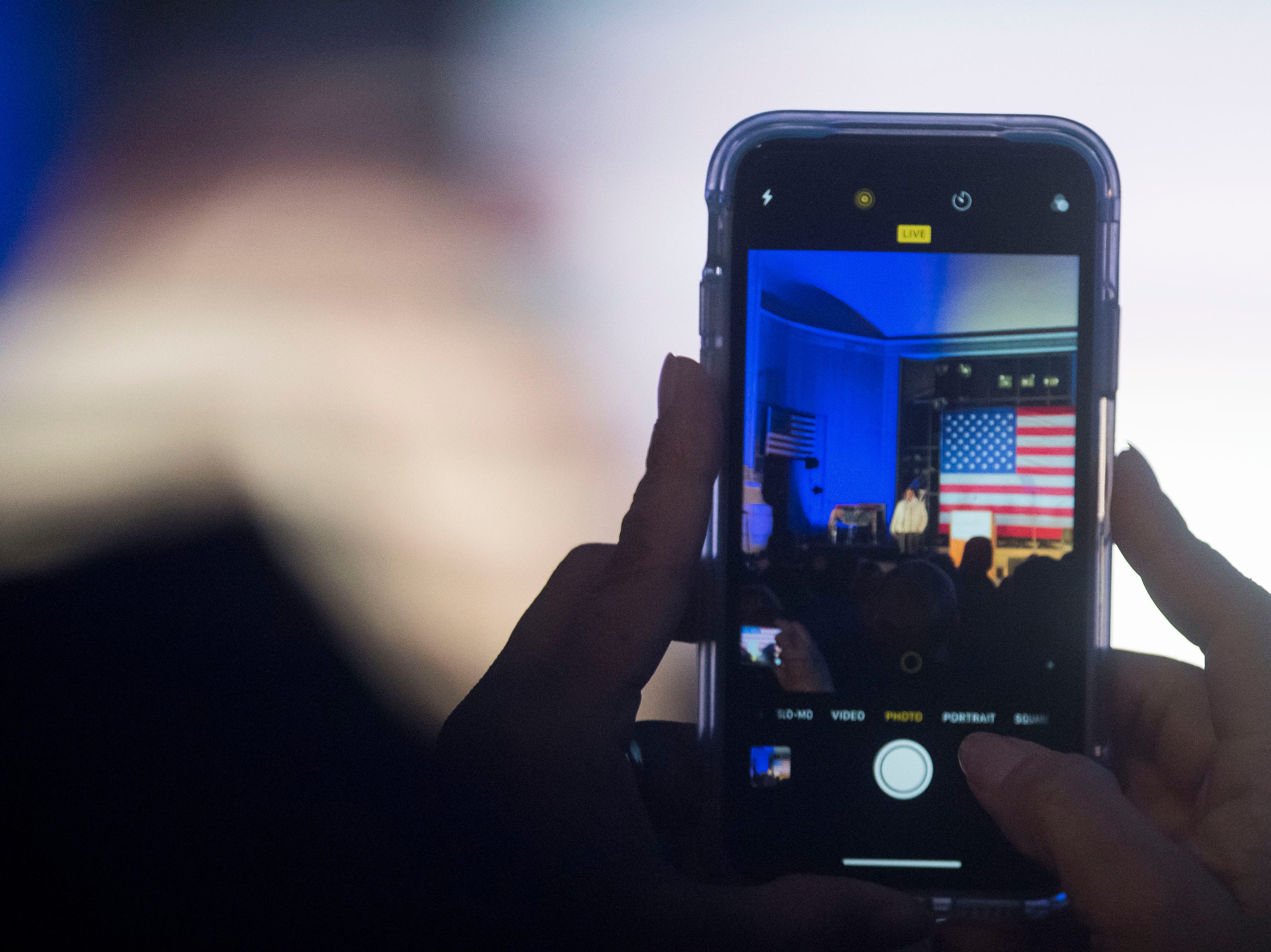 A rally participant takes video of the stage at the John Hickenlooper presidential campaign kick-off rally on Thursday, March 7, 2019, at the Greek Ampitheatre in Civic Center Park in Denver, Colo.
