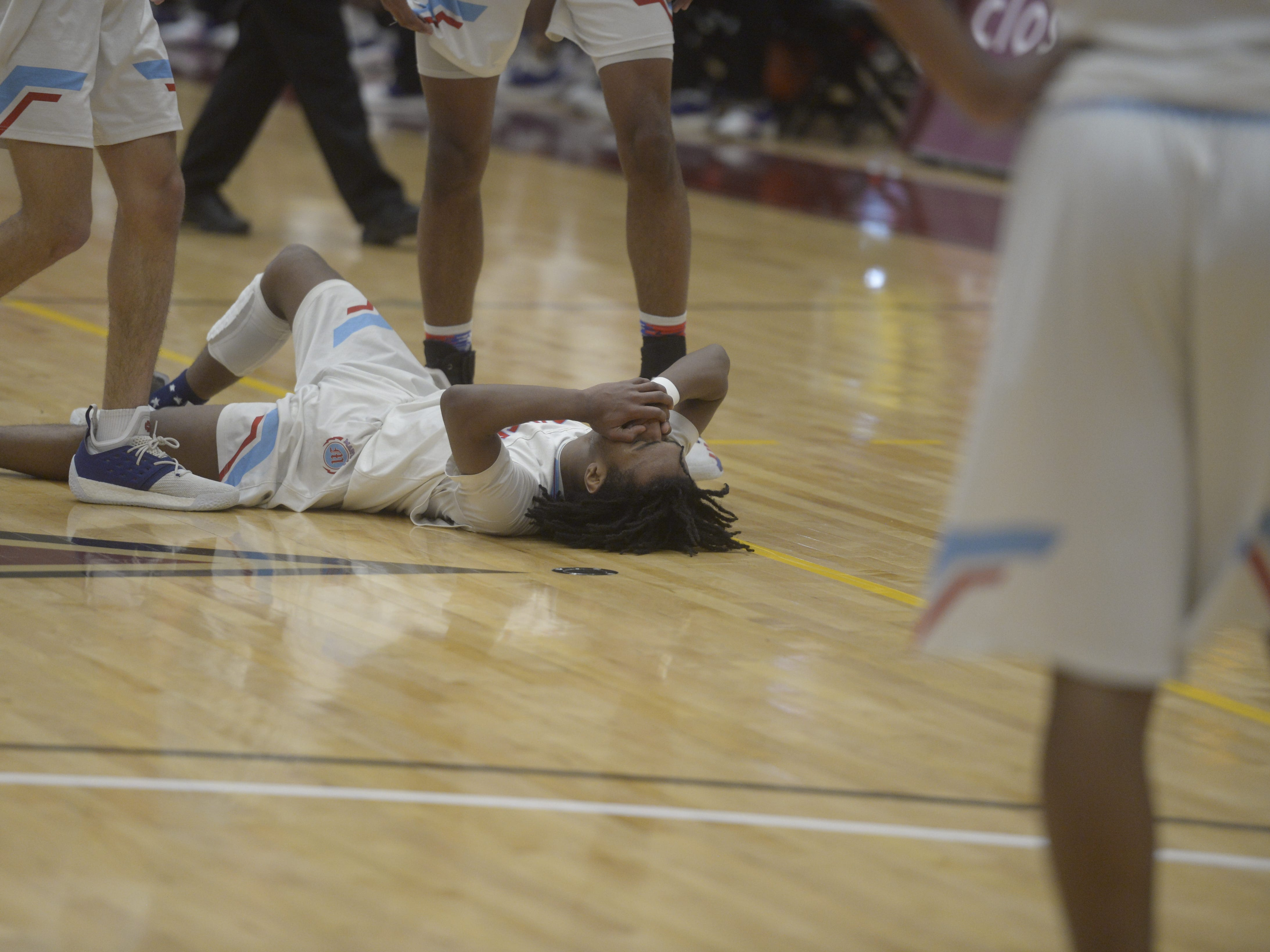 Manual guard Davion Davis lies on the floor after a collision during a Class 3A quarterfinals game against Resurrection Christian at the University of Denver on Thursday, March 7, 2019.