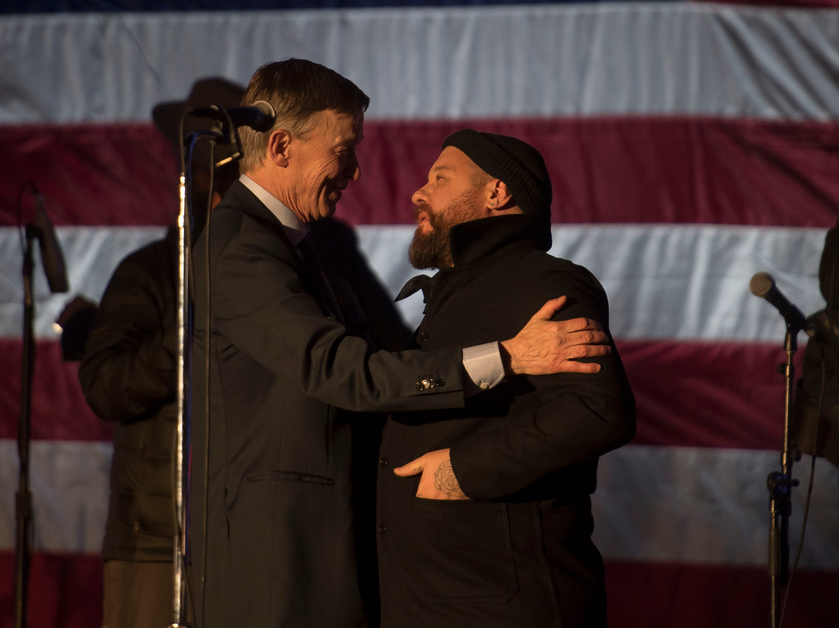 Former Colorado governor and current 2020 election year Presidential candidate John Hickenlooper shares a moment with Nathaniel Rateliff of the band Nathaniel Rateliff & The Night Sweats during HIckenlooper's presidential campaign kick-off rally on Thursday, March 7, 2019, at the Greek Ampitheatre in Civic Center Park in Denver, Colo.
