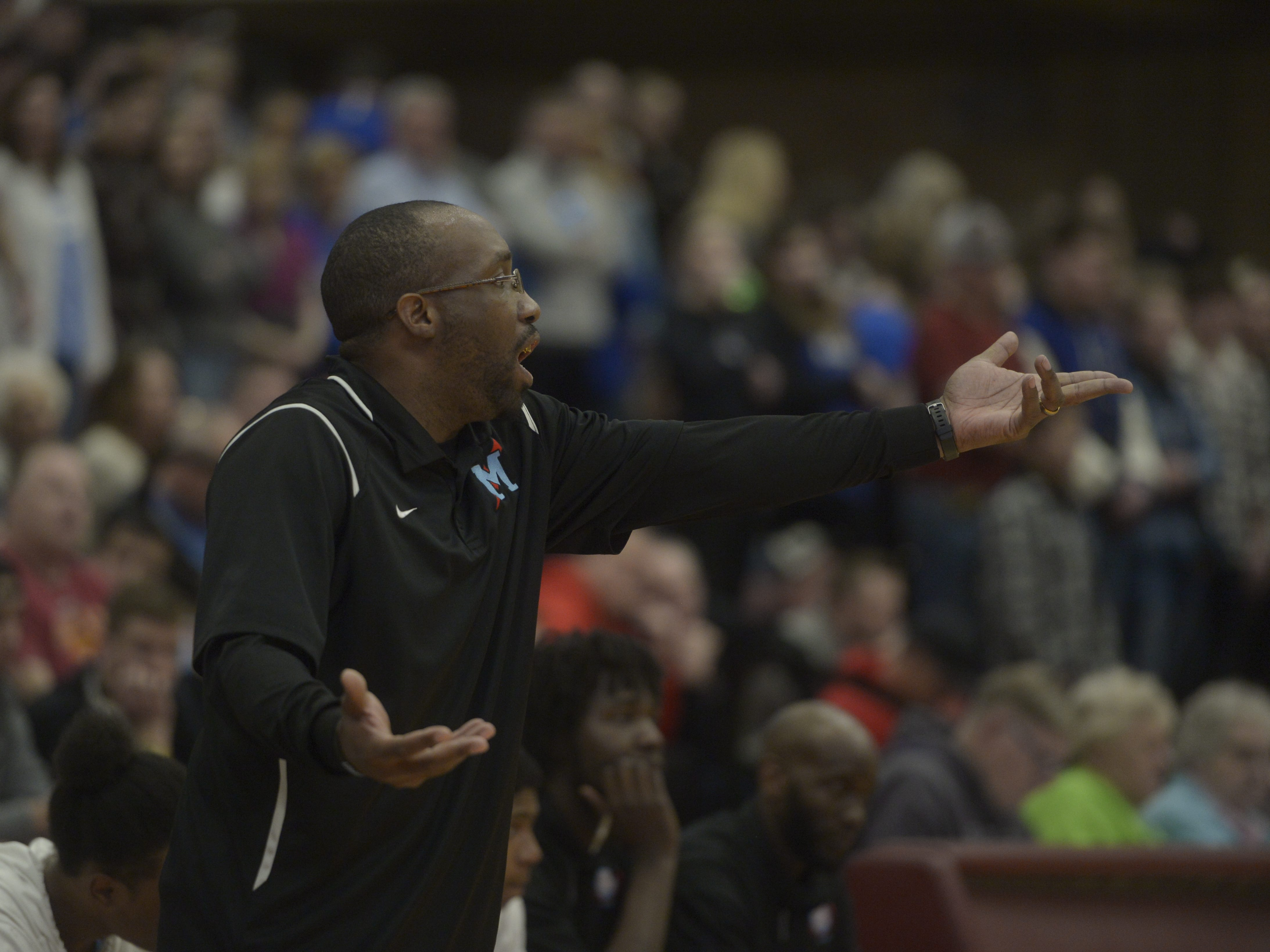 Manual basketball coach Omar Henry gives instructions to his team during a Class 3A quarterfinals game at the University of Denver on Thursday, March 7, 2019.