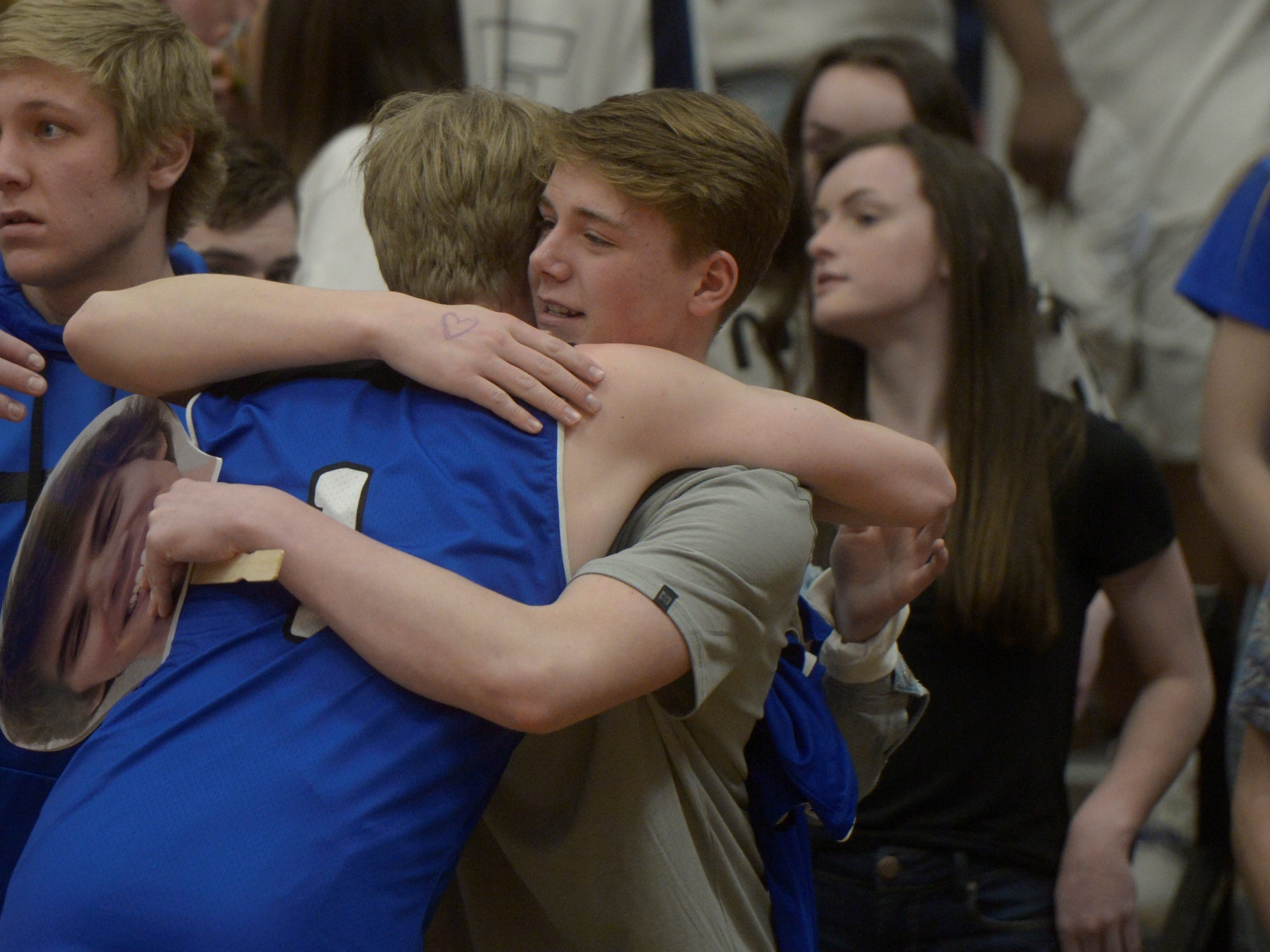 Resurrection Christian basketball guard Logan James gets a hug after a Class 3A quarterfinals game against Manual at the University of Denver on Thursday, March 7, 2019.