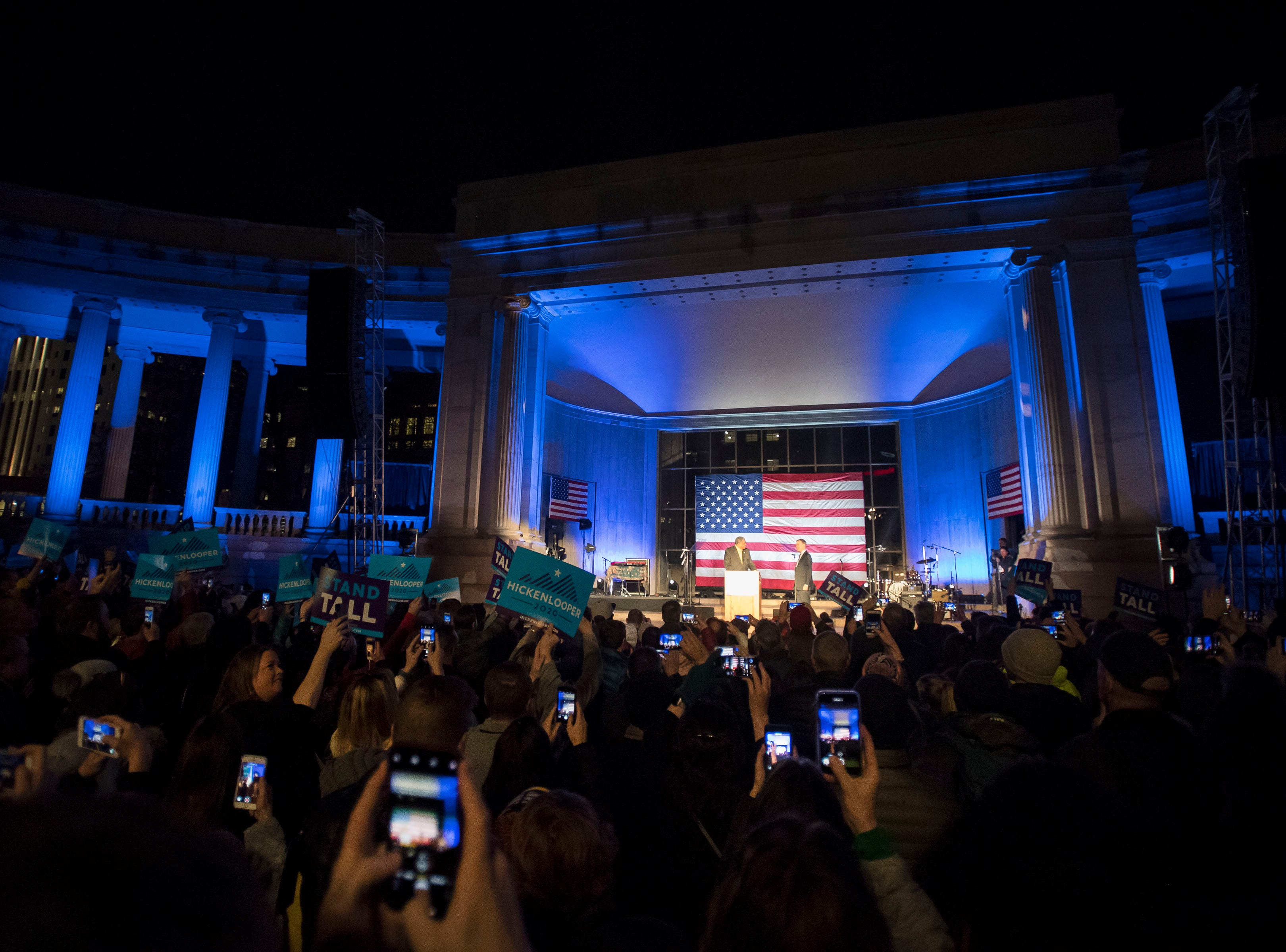 Rally participants record the moment on their phones as former Denver mayor Wellington Webb welcomes former Colorado governor John Hickenlooper on stage at his presidential campaign kick-off rally on Thursday, March 7, 2019, at the Greek Ampitheatre in Civic Center Park in Denver, Colo.