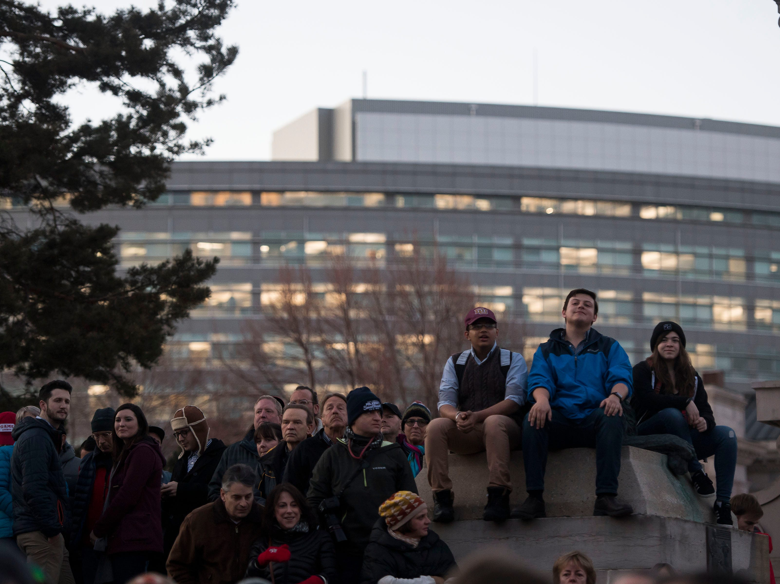 Rally participants sit around the outside of the amphitheater at the John Hickenlooper presidential campaign kick-off rally on Thursday, March 7, 2019, at the Greek Ampitheatre in Civic Center Park in Denver, Colo.