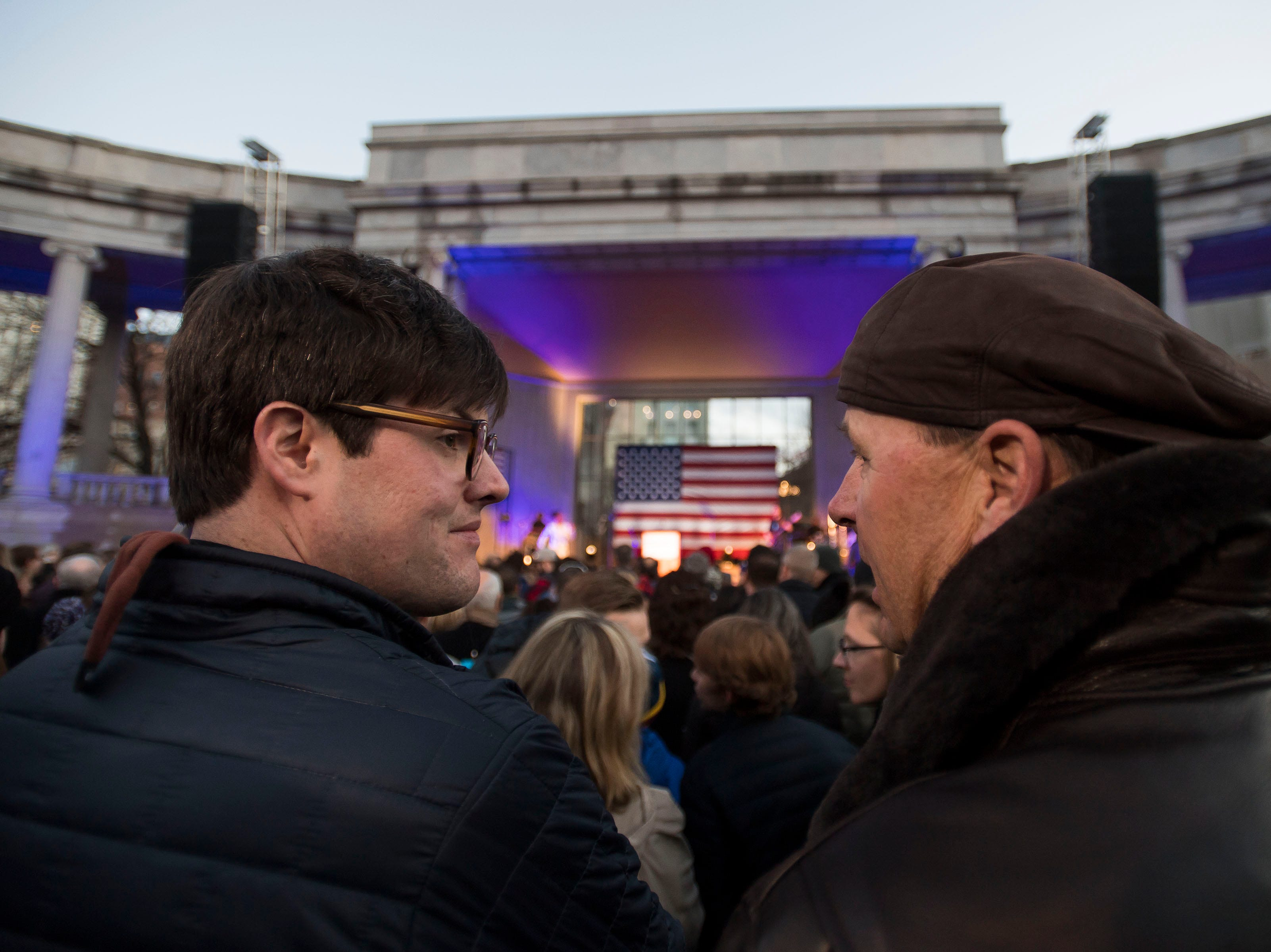 Peter Dea, right, and Kevin Schoelzel talk at the John Hickenlooper presidential campaign kick-off rally on Thursday, March 7, 2019, at the Greek Ampitheatre in Civic Center Park in Denver, Colo.