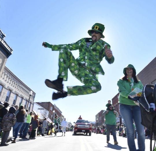 Leprechaun Travis Blasier of Carlsville leaps into the air while doing his Irish jig as he marches in the 2018 St. Patrick's Day parade in Sturgeon Bay.