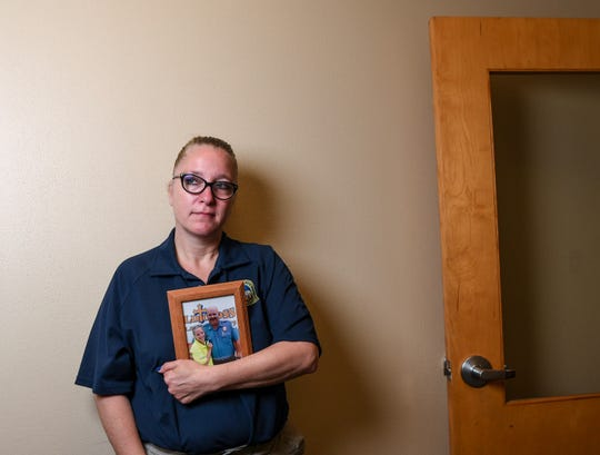 """Sheila Kaiser holds a photograph of her husband James, who took his life in 2016. """"We need to realize they're not going to reach out for help. We have to reach out to them,"""" Kaiser said about when co-workers sense something is not right."""