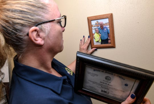 "Sheila Kaiser looks at a photograph of her husband James, who took his life in 2016. ""We need to realize they're not going to reach out for help. We have to reach out to them,"" Kaiser said about when co-workers sense something is not right."
