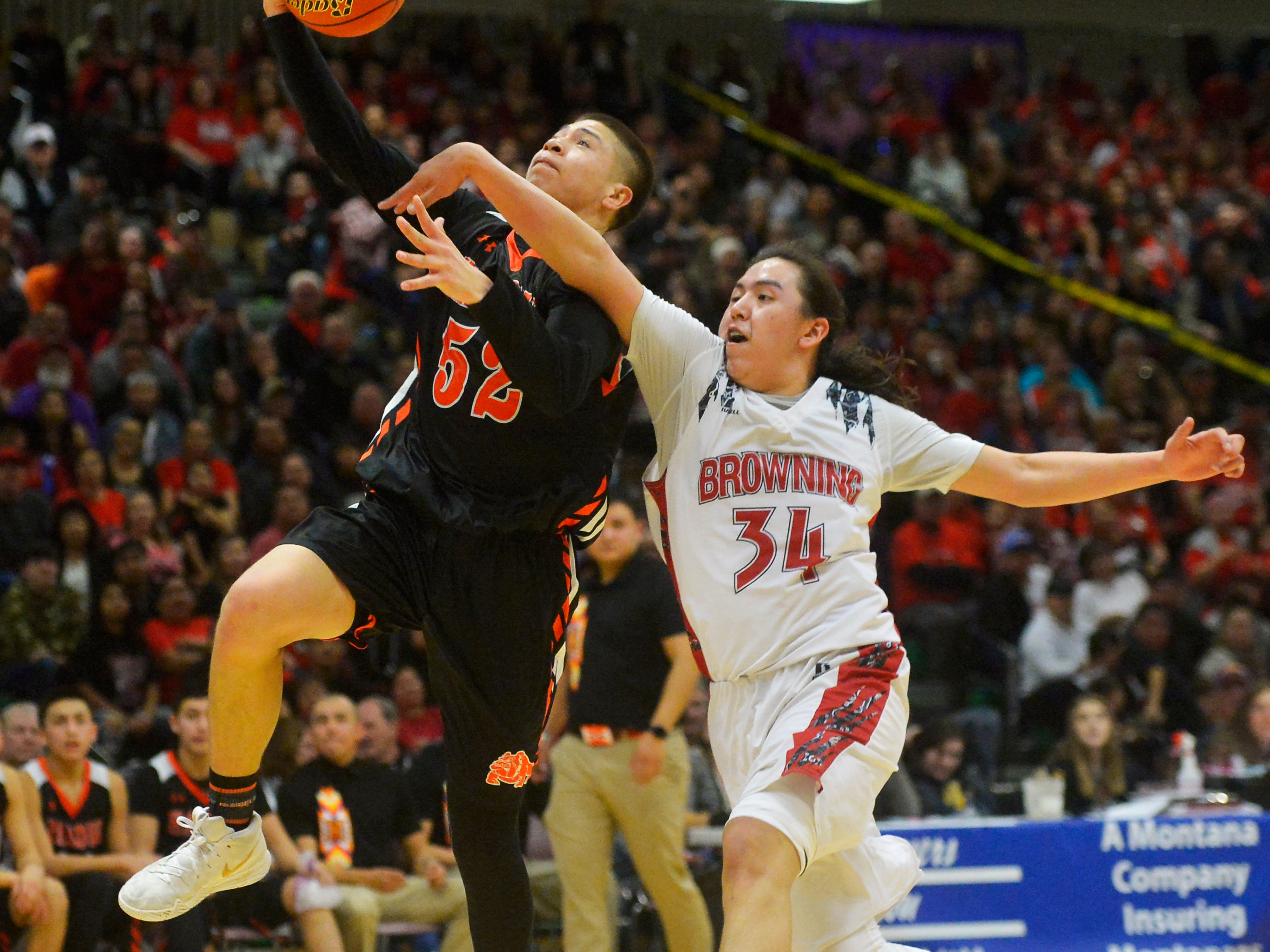 Hardin's Famous Lefthand goes in for a layup as Browning's Deion Mad Plume defends during the Class A State Basketball Tournament in the Four Seasons Arena, Thursday.