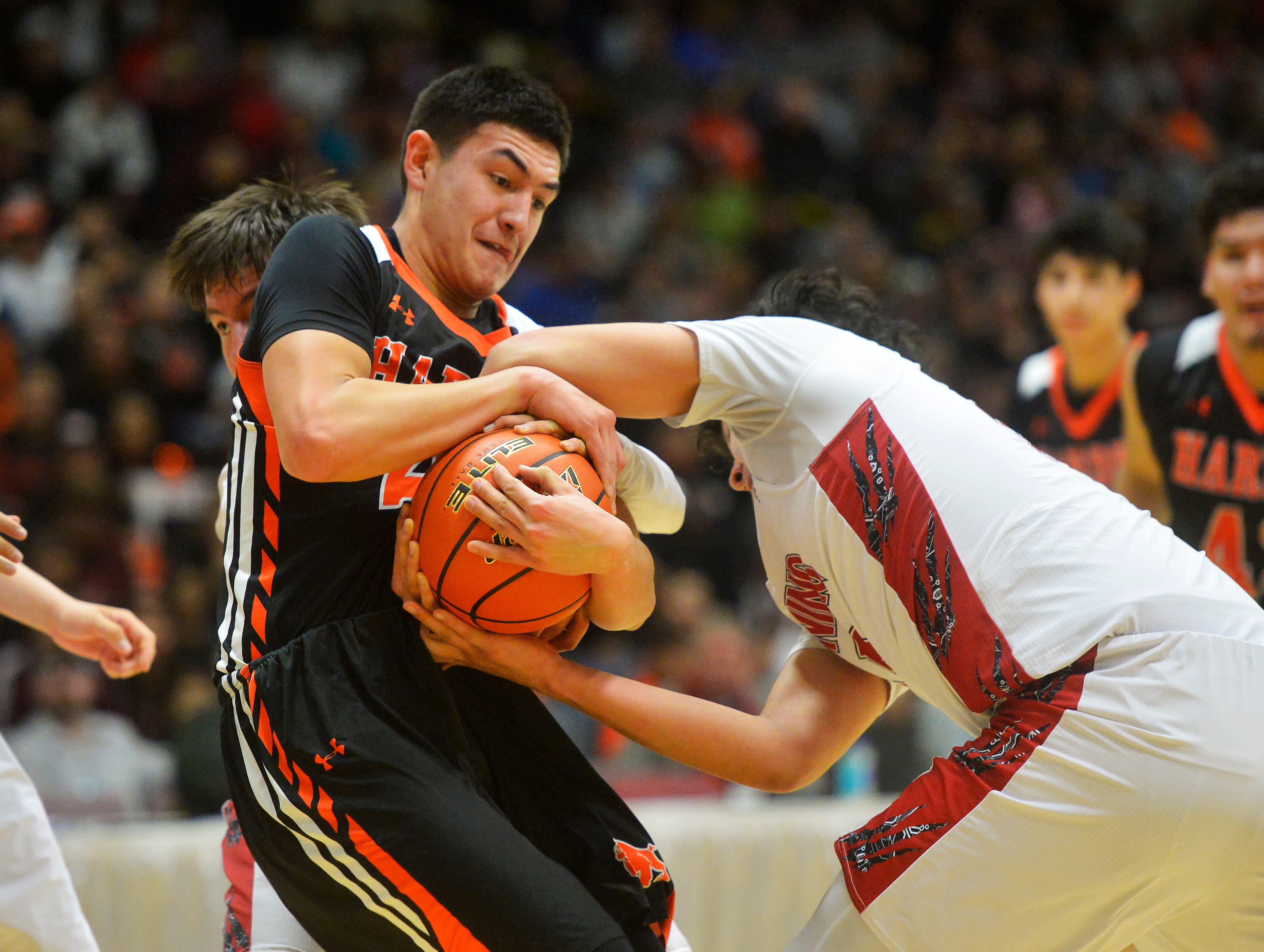 Hardin's Cayden Redfield battles for possession with Browning's Tyree Whitcomb during the Class A State Basketball Tournament in the Four Seasons Arena, Thursday.