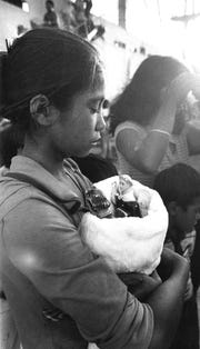 Thirteen-year-old Lucy Aldan in May 1981 cradles religious statues she carried with her from her home island of Pagan, which was evacuated when Mt. Pagan erupted.