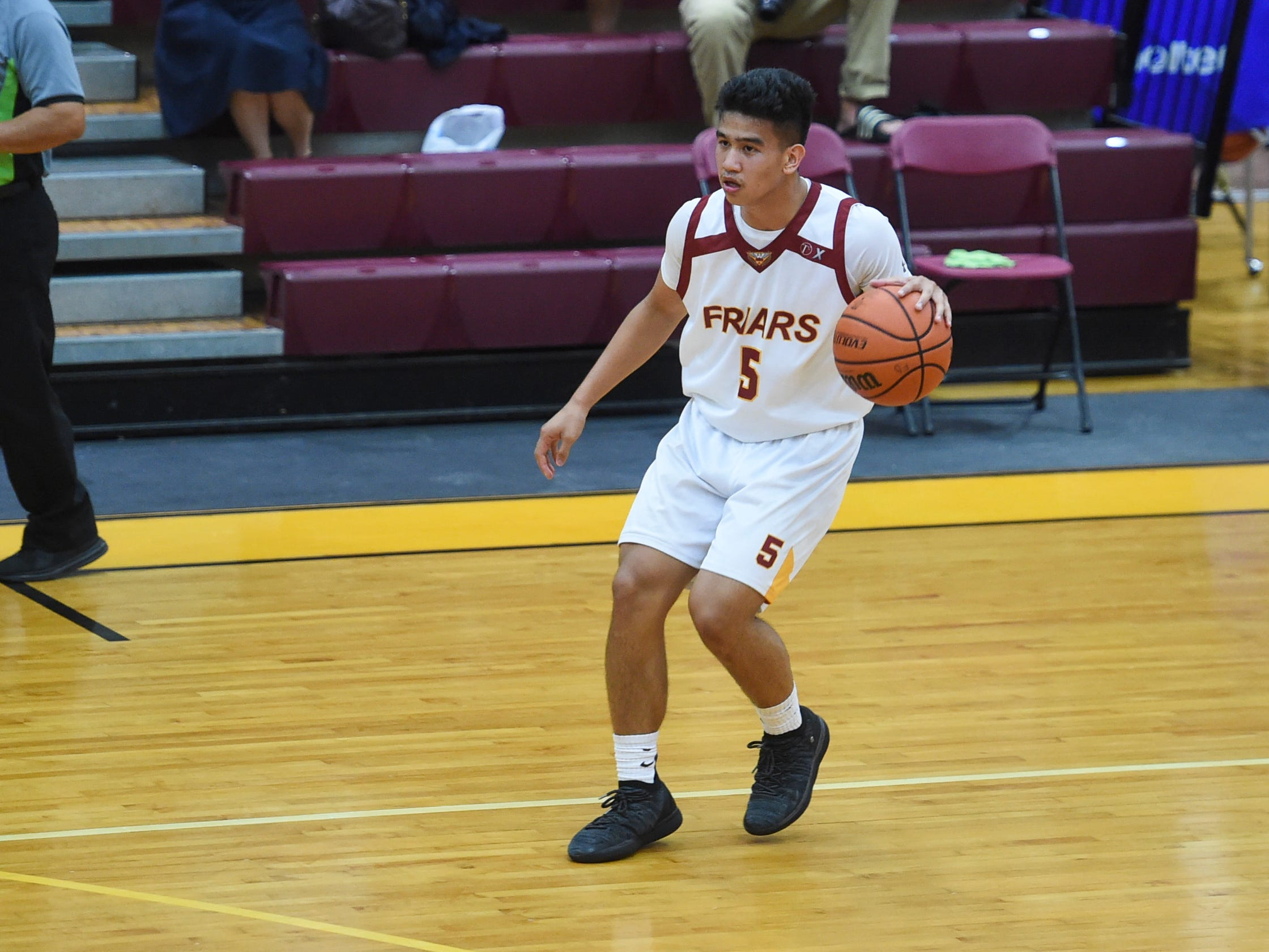 Father Duenas player Raymond Soriano (5) brings the ball down the court against the John F Kennedy Islanders during their IIAAG Boys' Basketball playoff game at the FD Phoenix Center, March 8, 2019. The Friars came up with the 64-62 win at the end of overtime after a close back-and-forth contest.