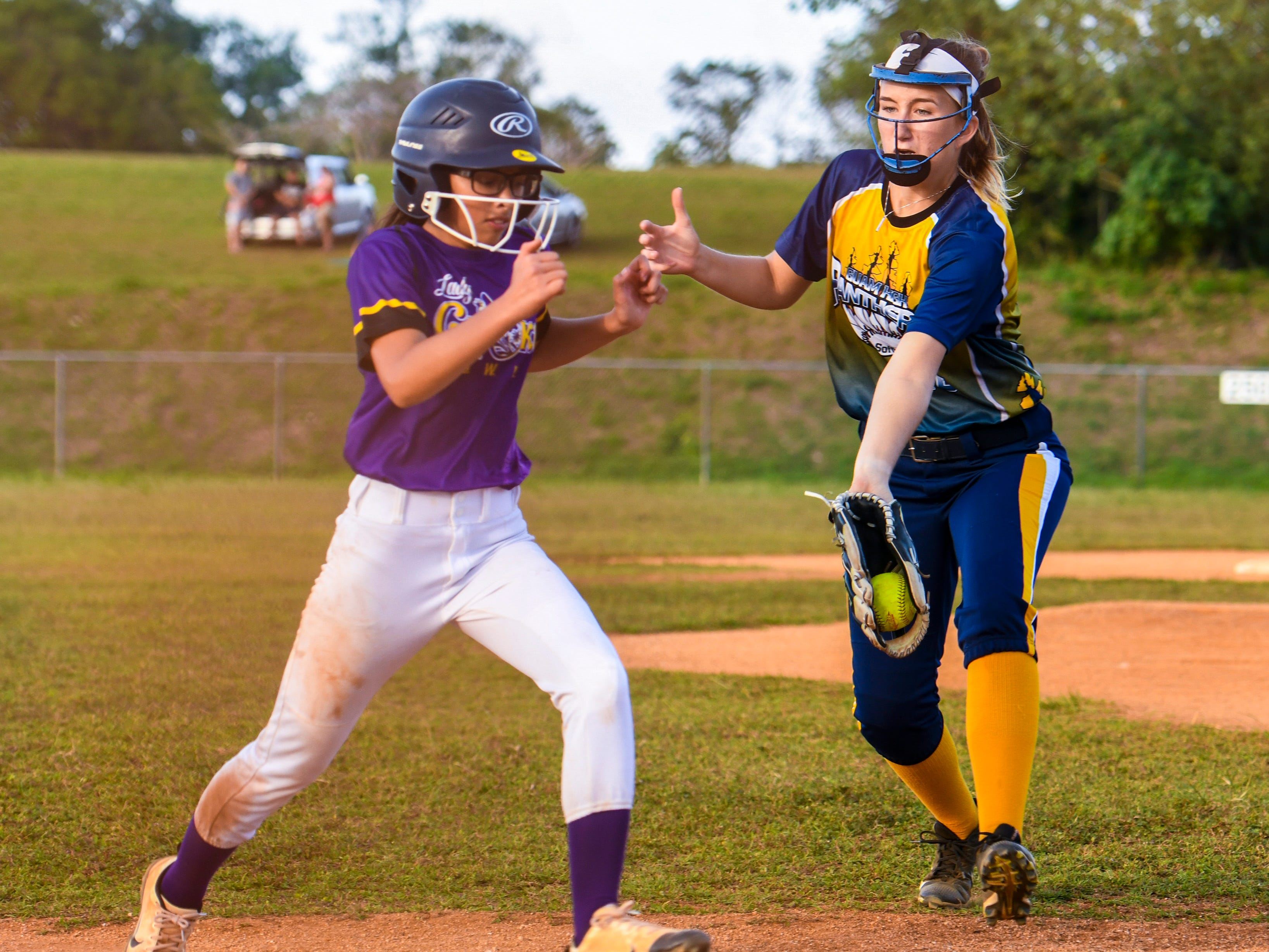 George Washington High School Geckos' Joresha Quichocho, slips by Guam High School Panthers' pitcher Alexis Blyth, on her sprint to home during an IIAAG girls softball game on the diamond at Okkodo High School in Dededo on Thursday, March 7, 2019.
