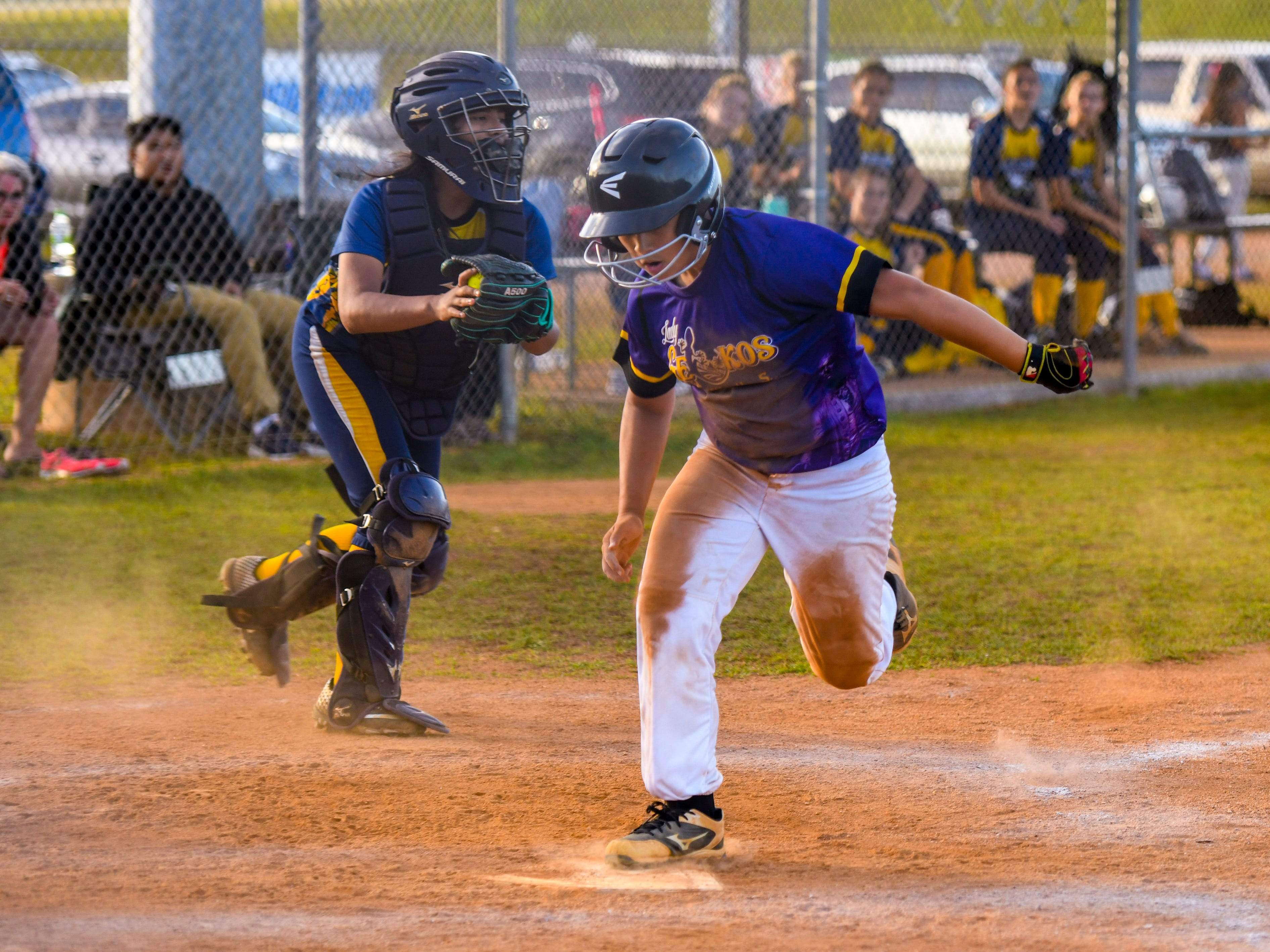 George Washington High School Geckos' Rocki Mesa makes it to homeplate to score a run after almost getting caught between bases during an IIAAG girls softball game against the Guam High School Panthers at Okkodo High School in Dededo on Thursday, March 7, 2019.