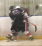 Jack Hutto, who is a defenseman for the Evansville Thunder, checks an opponent into the board. Hutto is a junior at Henderson County High School.