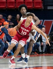 Indiana guard Rob Phinisee protects the ball from the defense of Illinois guard Andres Feliz, rear, during the first half of an NCAA college basketball game in Champaign, Ill., Thursday, March 7, 2019.