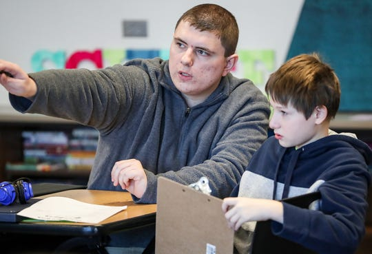 From right, sixth grader Ryan Grigsby works with one-on-one instructional assistant Caleb Bell during class at Noblesville East Middle School in Noblesville, Ind., Monday, March 4, 2019. Noblesville School district is leading the state in efforts to place students with special learning needs in general education classrooms and teach the same concepts as their peers.