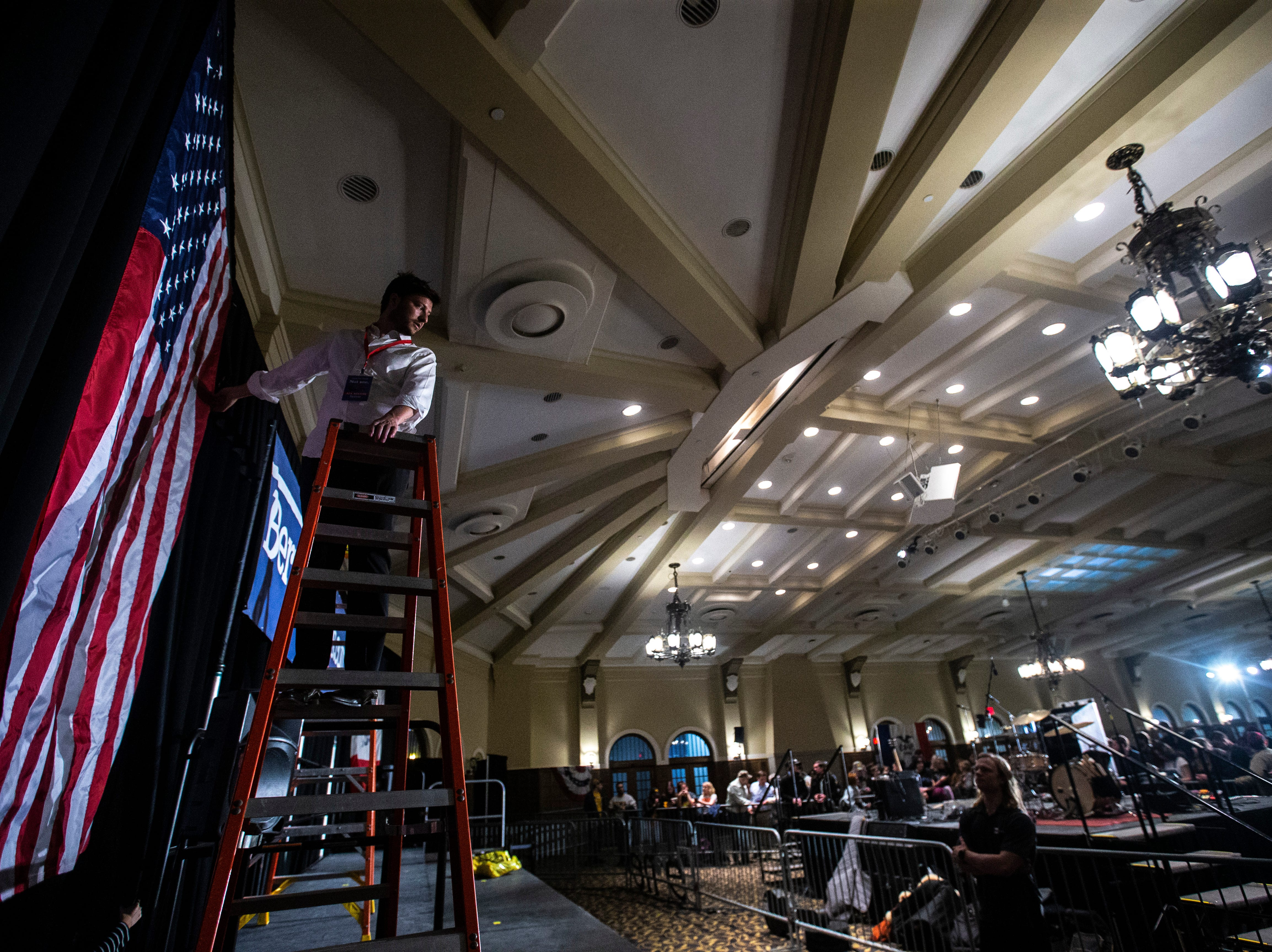 Staff adjust an American flag before U.S. Sen. Bernie Sanders, I-VT, speaks at an event during his first trip to the state ahead of the caucus, Friday, March 8, 2019, at the Iowa Memorial Union on the University of Iowa campus in Iowa City, Iowa.