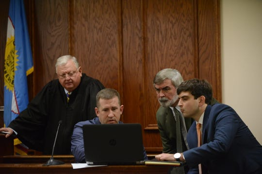 Judge Blake Anderson, far left, JPD Investigator Robert Groves, second to the left, attorney Daniel Taylor, second to the right and attorney William Milam look at police footage of the shooting during the preliminary hearing for the shooting of Travoris Bate in Jackson, Tenn. on March 7, 2019.