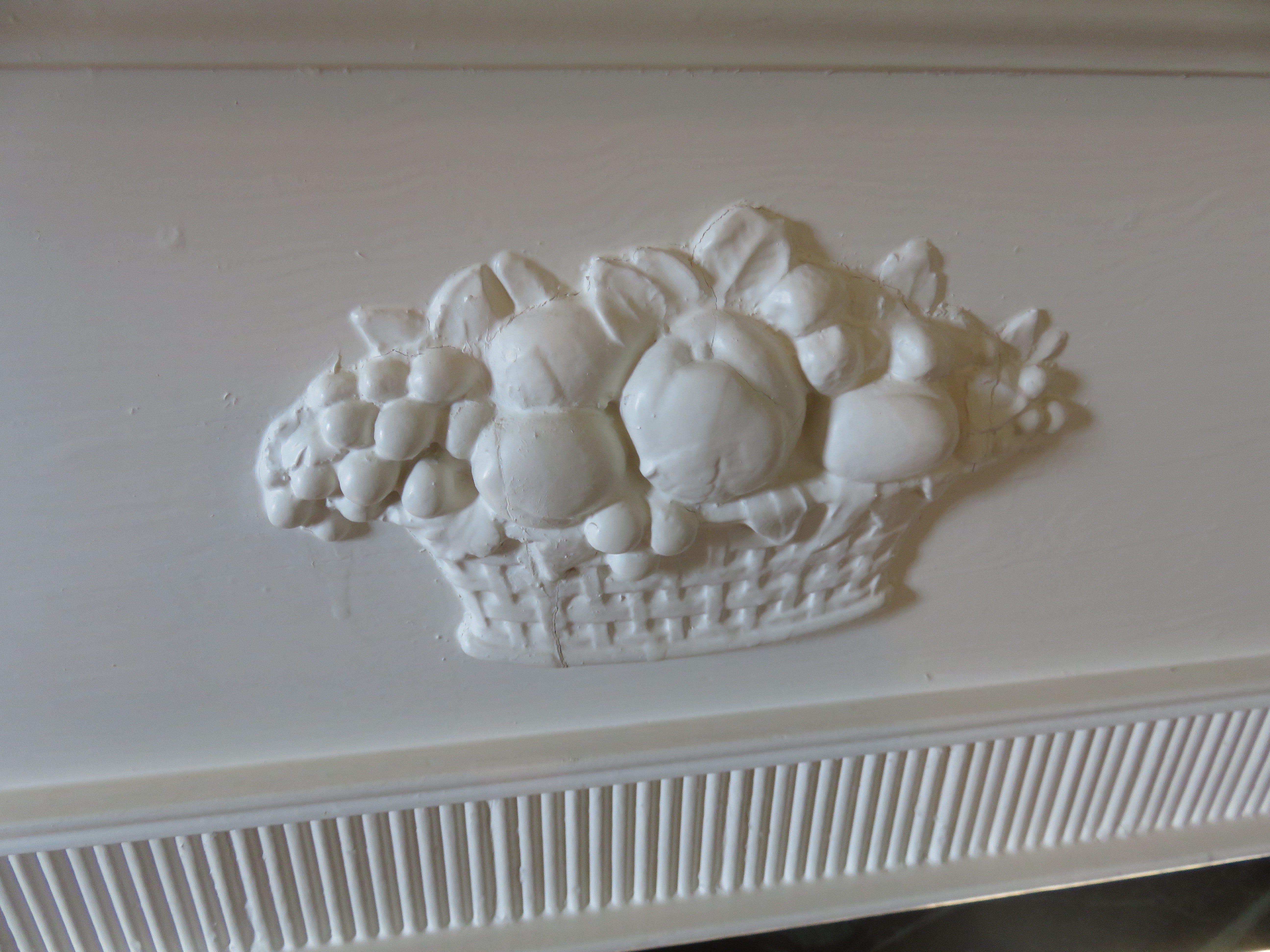 Harvest bowl depicted in detail on historic mantel.