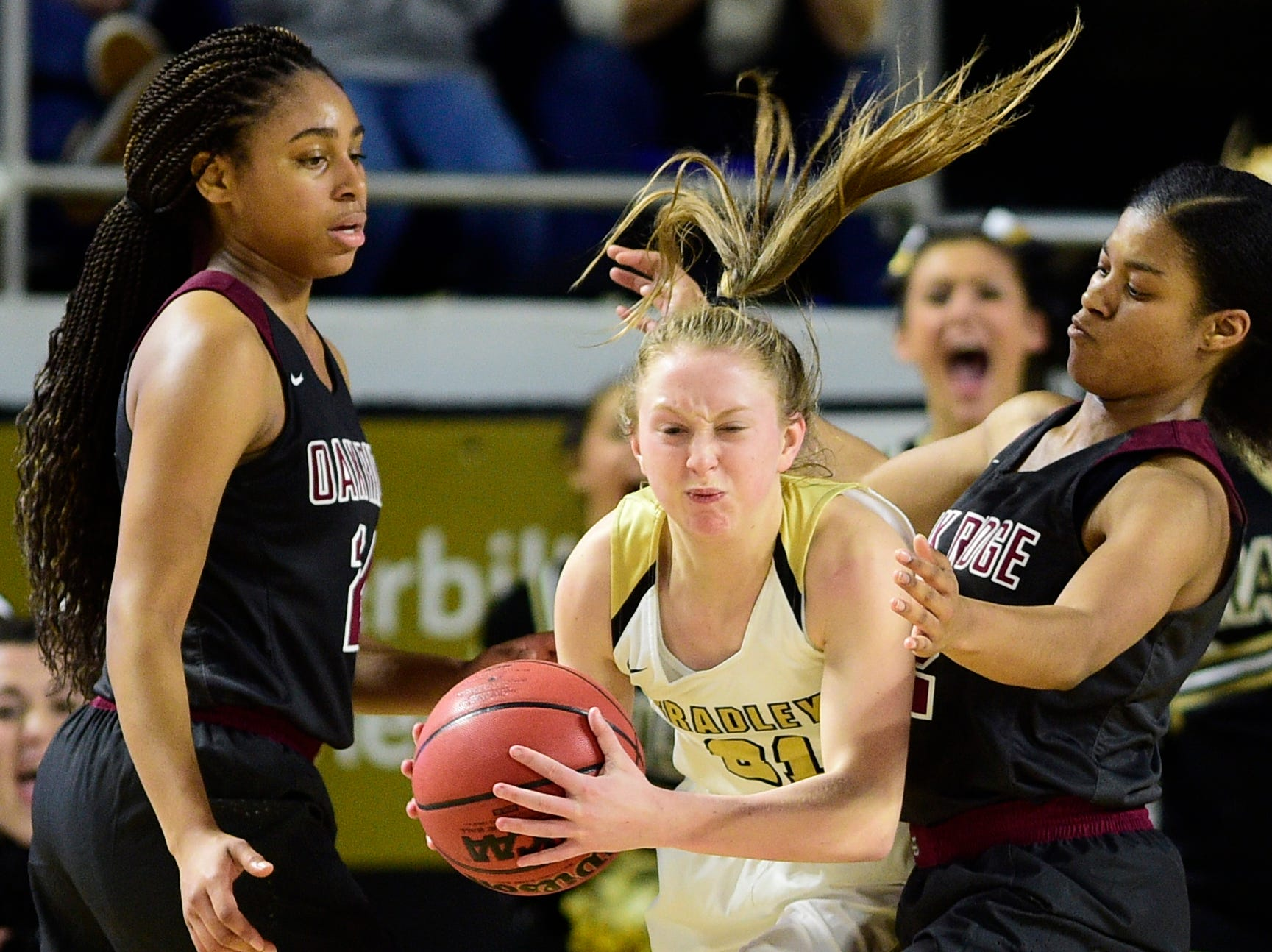 Bradley Central's Cambree Mayo (21) grabs the rebound past Oak Ridge's Jada Guinn (24) and Oak Ridge's Shatyrah Copeland (22) during a game between Oak Ridge and Bradley Central at the TSSAA girls state tournament at the Murphy Center in Murfreesboro, Tennessee on Friday, March 8, 2019.