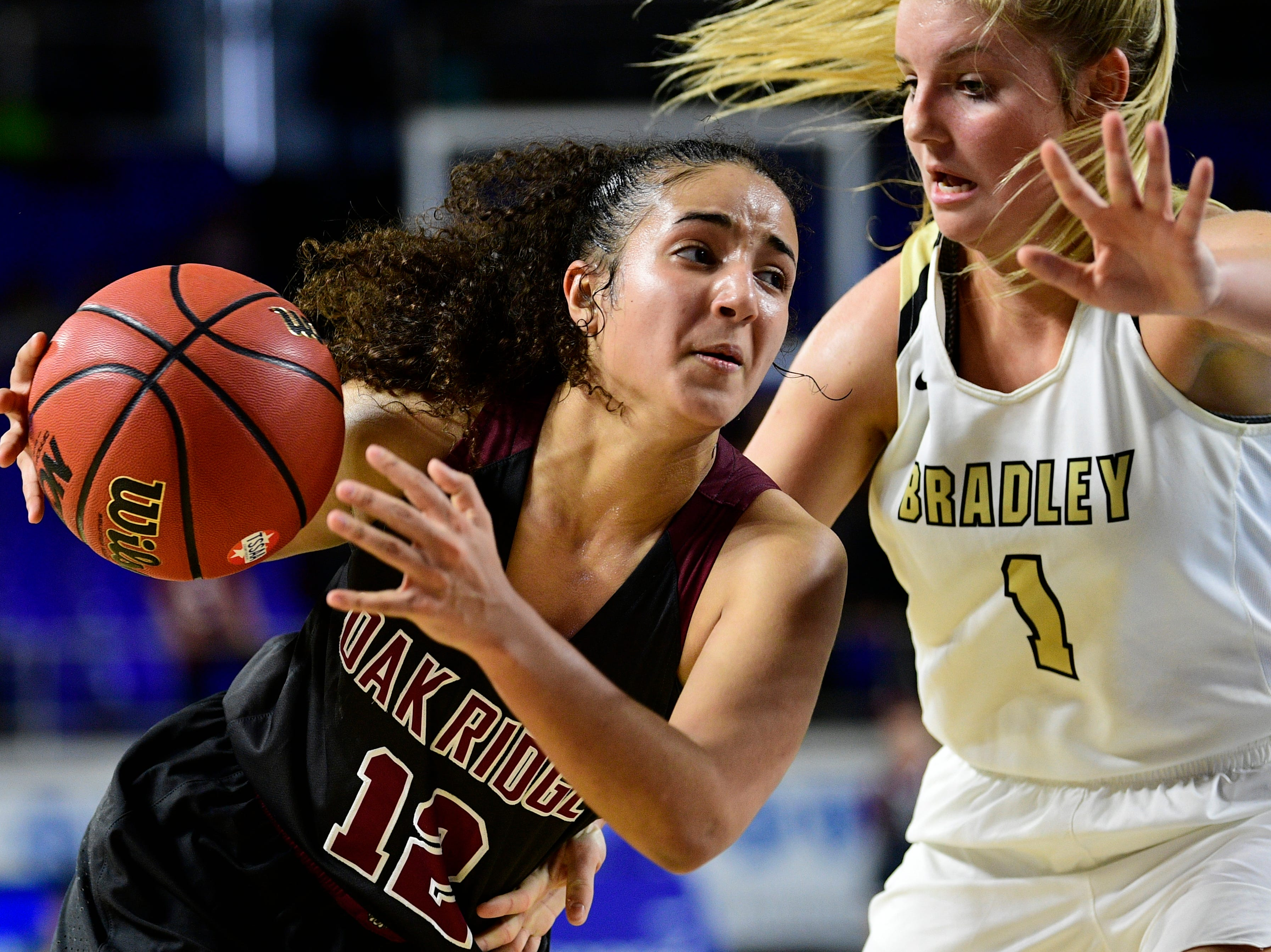 Oak Ridge's Brianna Dunbar (12) dribbles past Bradley Central's Kaleigh Hughes (1) during a game between Oak Ridge and Bradley Central at the TSSAA girls state tournament at the Murphy Center in Murfreesboro, Tennessee on Friday, March 8, 2019.