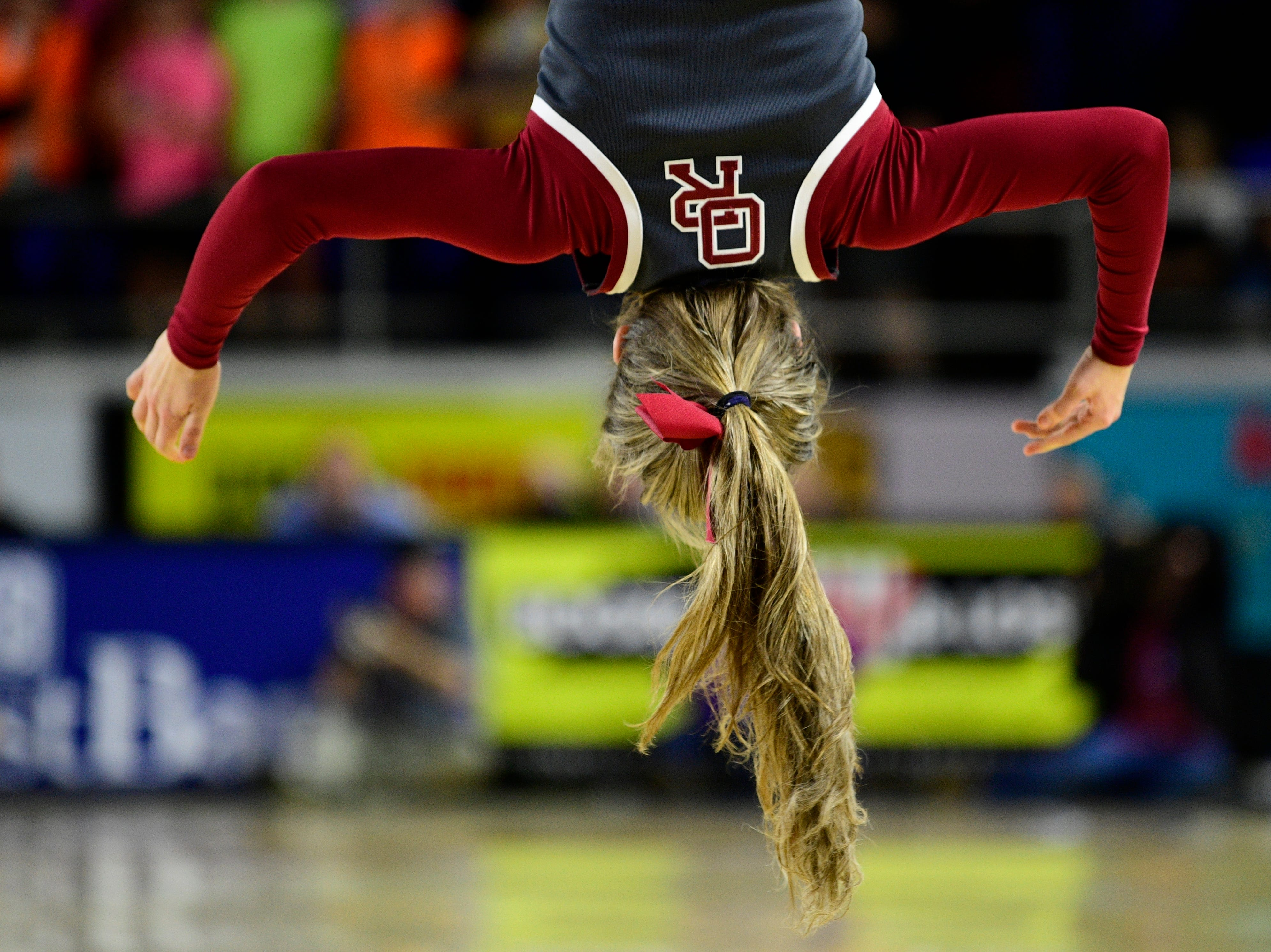 An Oak Ridge cheerleader performs a stunt during a game between Oak Ridge and Bradley Central at the TSSAA girls state tournament at the Murphy Center in Murfreesboro, Tennessee on Friday, March 8, 2019.