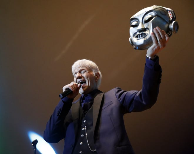 """Dennis DeYoung holds up a Kilroy mask as he sings """"Mr. Roboto"""" during a concert last year at the Ohio University Lancaster Wendel Concert Stage in Lancaster. DeYoung performed the first headline concert of the 2018 Lancaster Festival."""