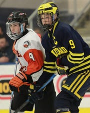 Joey Larson (right) of Hartland and Nick Marone of Birmingham Brother Rice keep close tabs on one another in a state Division 2 hockey semifinals on Thursday, March 7, 2019 at USA Hockey Arena.