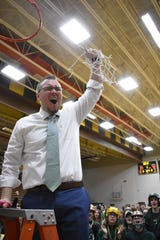 Howell coach Nick Simon celebrates after cutting down the net following a 42-37 victory over Oxford in the regional basketball championship game on Thursday, March 7, 2019.