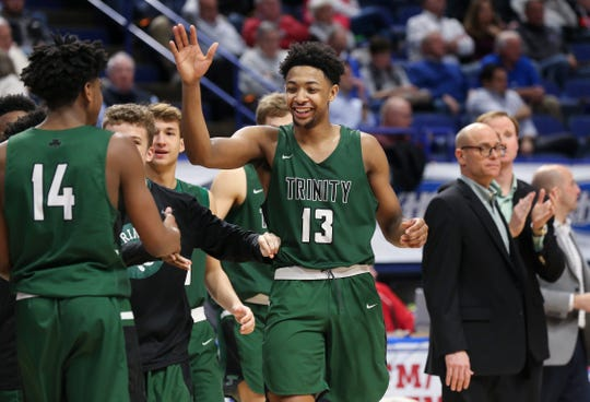 Trinity's David Johnson (13) celebrated a run with his teammates against Ashland Blazer during the Sweet 16 Tournament at Rupp Arena in Lexington.  Trinity won 60-30.