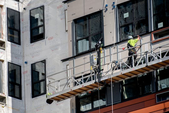 A man works on the exterior of the Center City District project on Friday, March 8, 2019, in East Lansing.