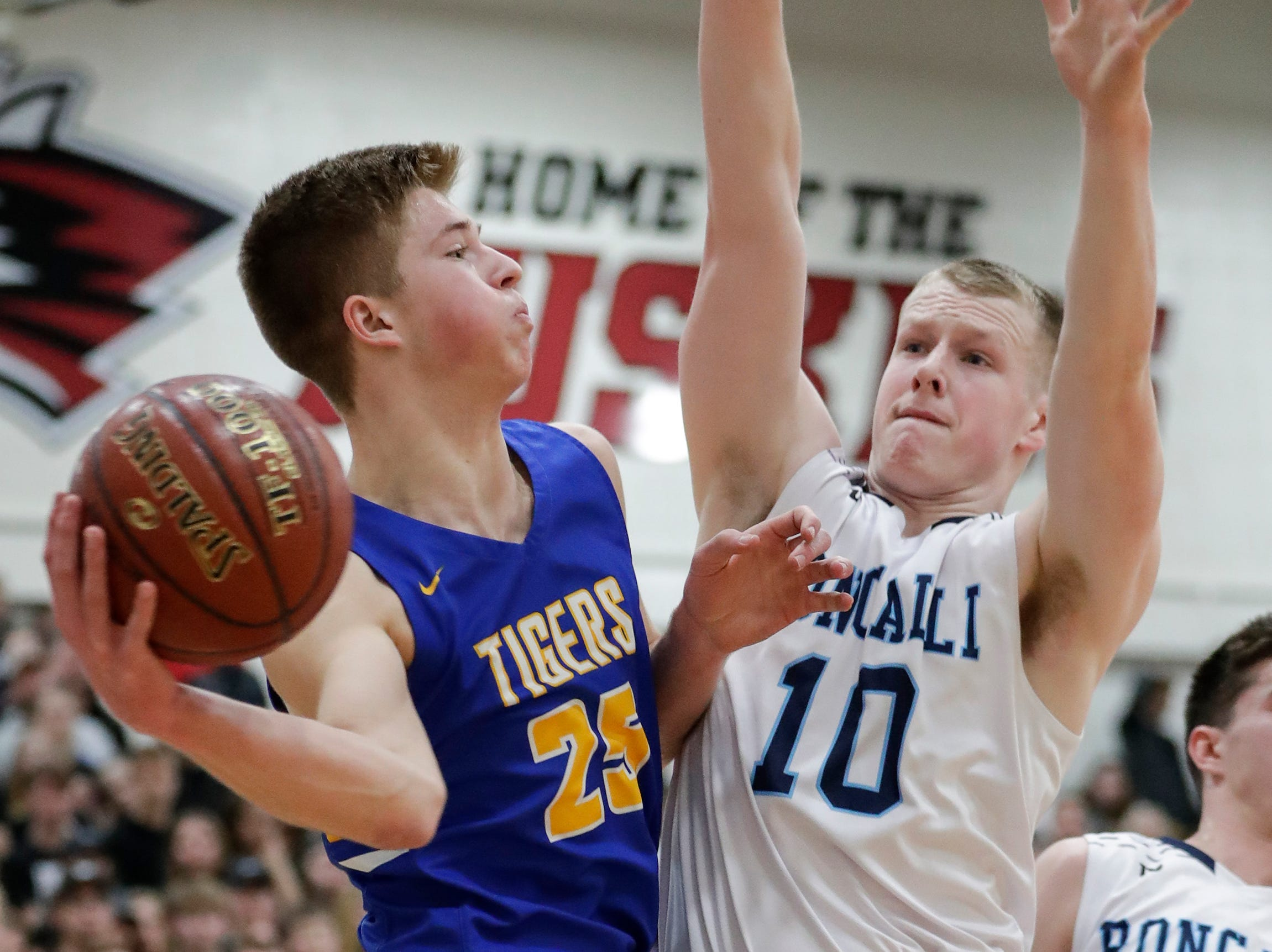 Howards Grove's Jack Baldwin (25) looks for an open teammate as he gets pressure from Roncalli's Matt Le Vene (10) during a WIAA Division 4 sectional semifinal at New Holstein High School Thursday, March 7, 2019, in New Holstein, Wis. Joshua Clark/USA TODAY NETWORK-Wisconsin