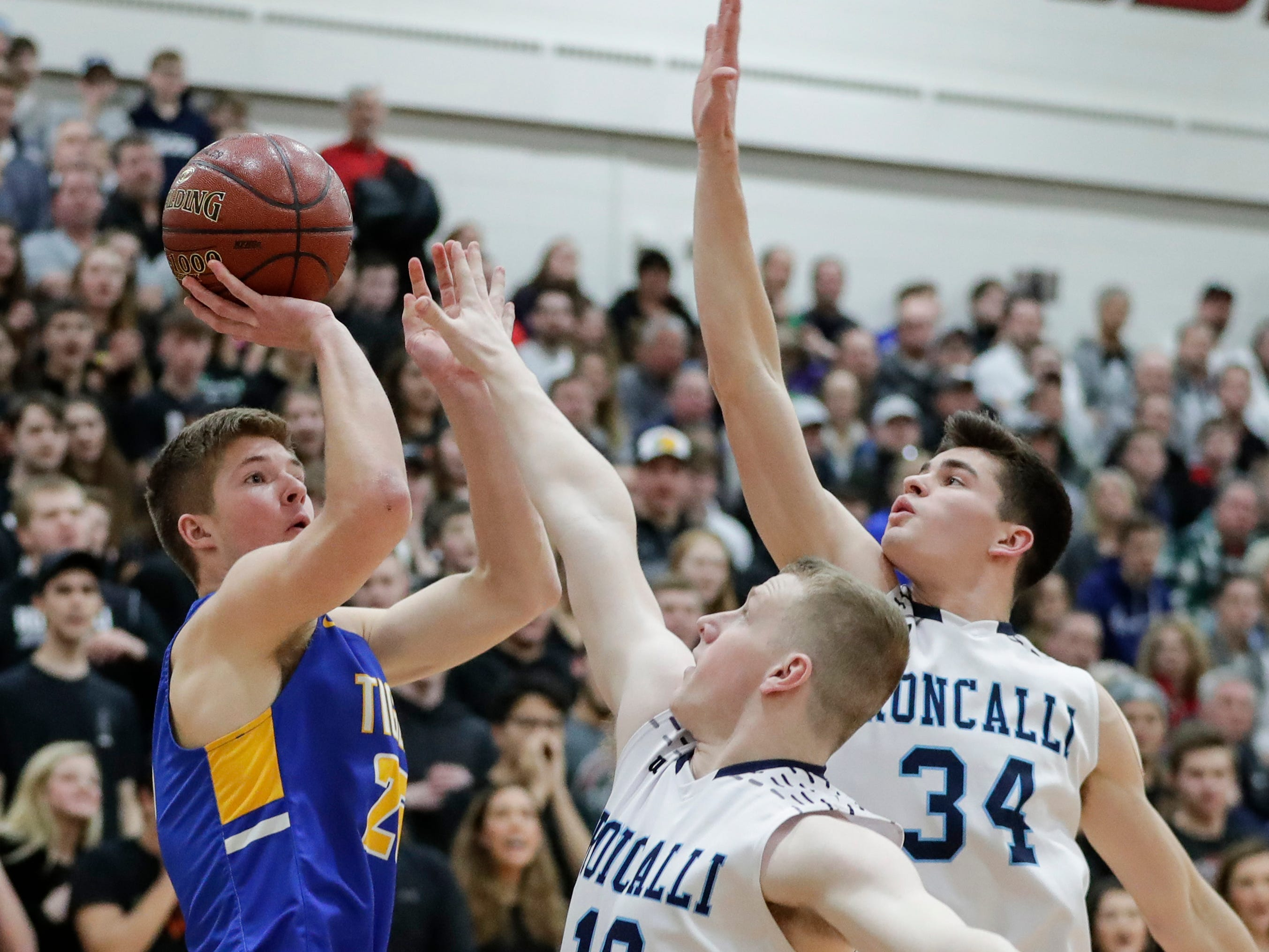 Howards Grove's Jack Baldwin (25) puts up a shot contested by Roncalli's Matt Le Vene (10) and Ian Behringer (34) in a WIAA Division 4 sectional semifinal at New Holstein High School Thursday, March 7, 2019, in New Holstein, Wis.
