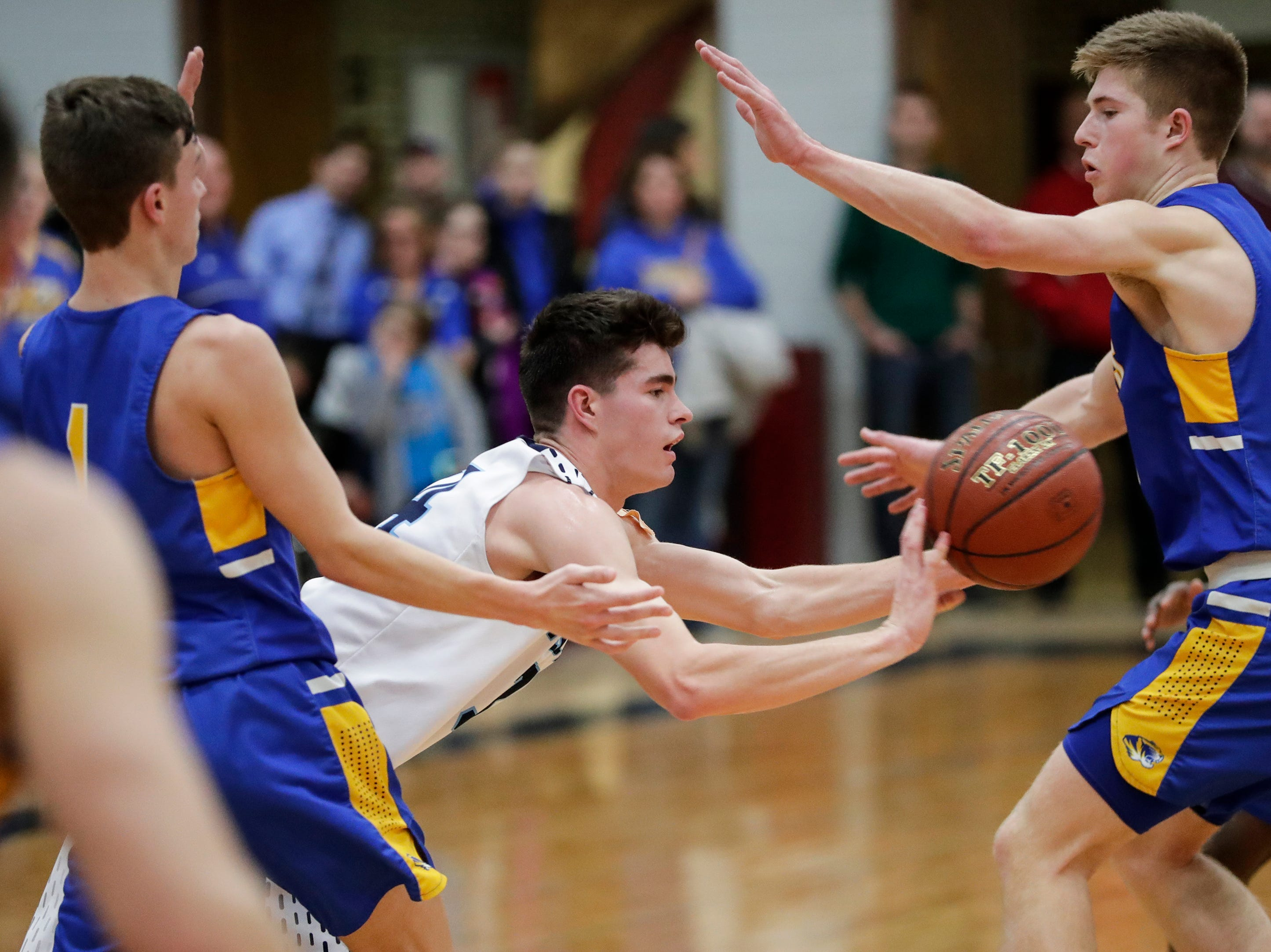 Roncalli's Ian Behringer (34) shovels off a pass against Howards Grove in a WIAA Division 4 sectional semifinal at New Holstein High School Thursday, March 7, 2019, in New Holstein, Wis. Joshua Clark/USA TODAY NETWORK-Wisconsin