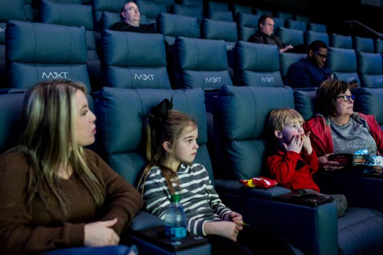 From left, Haley Moak and her children, Randi Rae, 7, Parker, 3, and mother, Shelly Harrell, wait for the start of their movie at Malco Powerhouse Cinema Grill & Bar in 2019. Malco has closed all of its theaters due to the ongoing coronavirus outbreak.