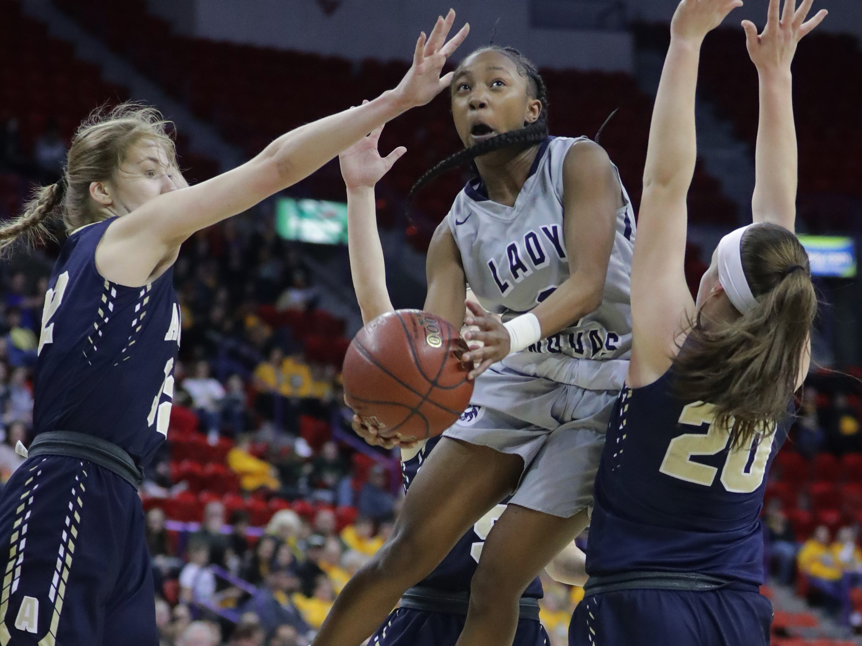 Three La Crosse Aquinas players converge on Milwaukee Academy of Science's Toniah Willimas (0) during the first half of their WIAA Division 4 state semifinal game Thursday, March 7, 2019, at the Resch Center in Ashwaubenon. La Crosse Aquinas beat Milwaukee Academy of Science 77-59.