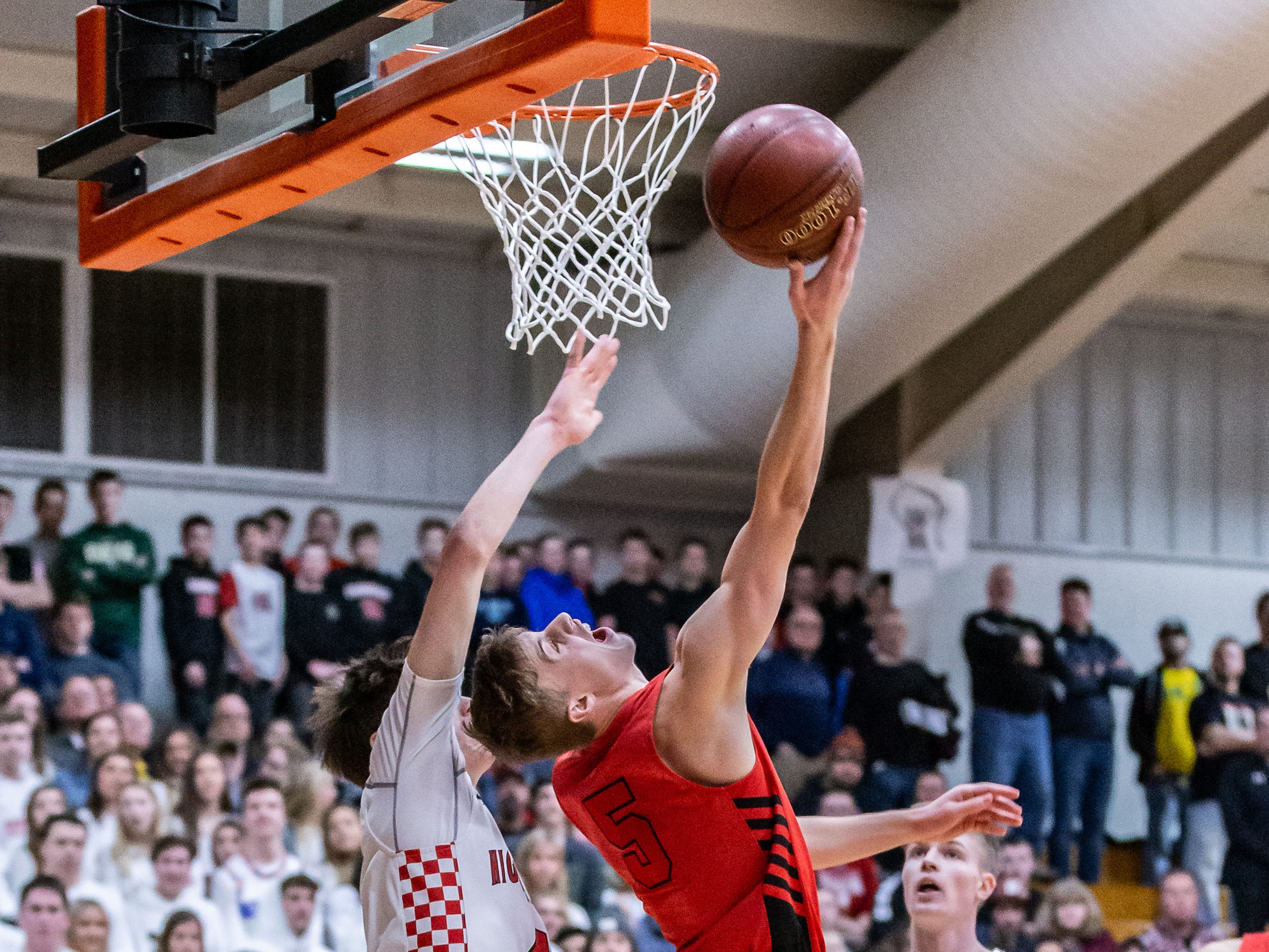Sussex Hamilton's Carson Smith (5) gets fouled on a reverse layup during the sectional semifinal against Homestead at Hartford on Thursday, March 7, 2019.