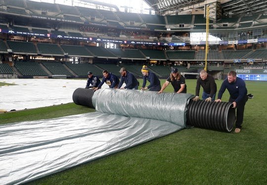 Grounds crew members roll up a tarp.