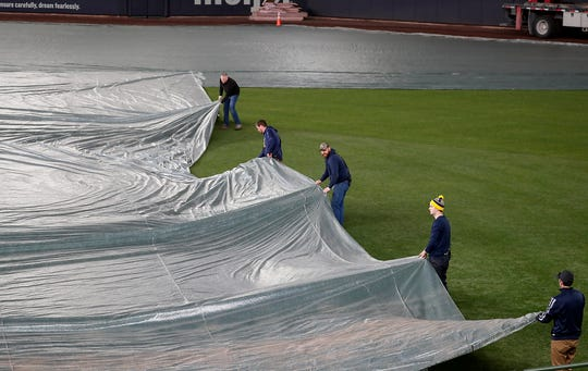 Grounds crew members remove a tarp at  Miller Park.