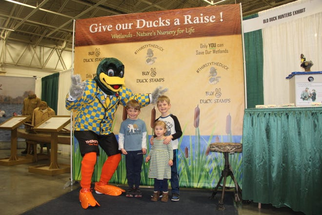 Thirsty the Duck poses with (left to right) Nathan, Anna and Matthew Prager of Waukesha at Bryan Muche's Old Duck Hunters Exhibit at the Milwaukee Journal Sentinel Sports Show. Muche has resurrected Thirsty from a 1960s Wisconsin-based campaign to raise funds and purchase wetlands to benefit waterfowl and other wildlife.