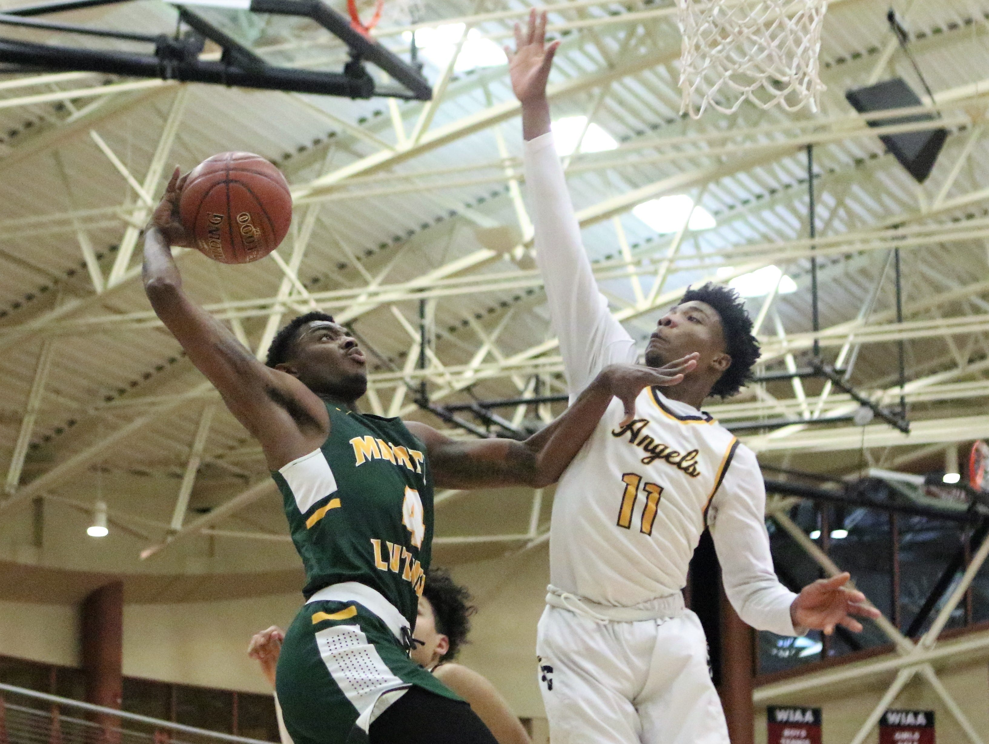 Martin Luther forward Xzavier Jones (left) attempts to go up for a dunk while defended by Racine St. Catherine's guard Tyrese Hunter during a WIAA sectional semifinal on March 7, 2019.
