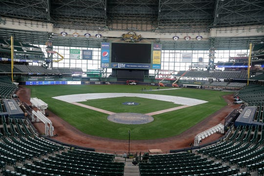 The field looks ready to go for baseball at Miller Park as grounds crew members remove tarps.