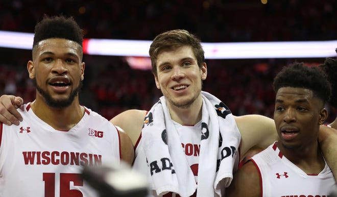 """Wisconsin seniors Charles Thomas (from left), Ethan Happ and Khalil Iverson sing one final postgame rendition of """"Varsity"""" after the Badgers beat Iowa."""