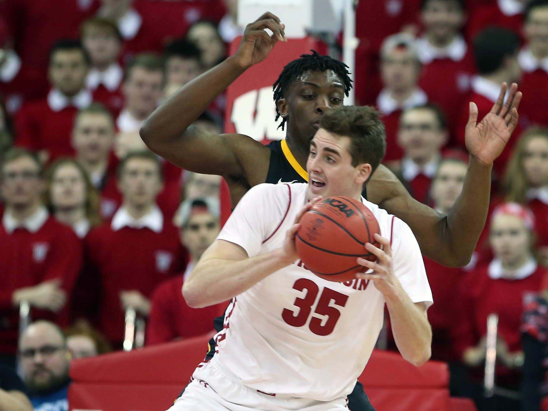 Badgers forward Nate Reuvers ponders his options while being guarded by Iowa forward Tyler Cook on Thursday night.