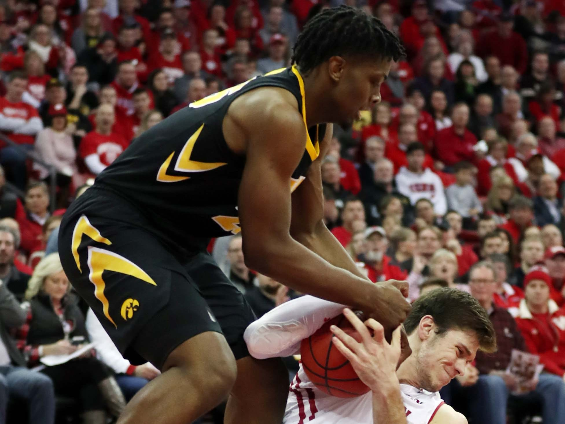 Badgers forward Ethan Happ tries to muscle a rebound away from Iowa forward Tyler Cook.